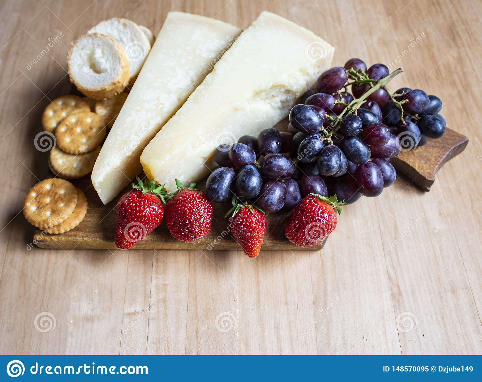 Τυρί με τα σταφύλια και τις φράουλες, την κροτίδα, τα καρύδια, τα φρούτα και τα καρύδια Τυρί σε ένα ορατό υπόβαθρο r