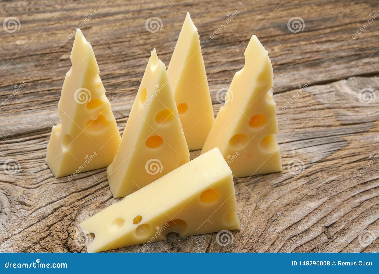 Τυρί με τις τρύπες μεγάλες και μικρές στο ξύλινο υπόβαθρο