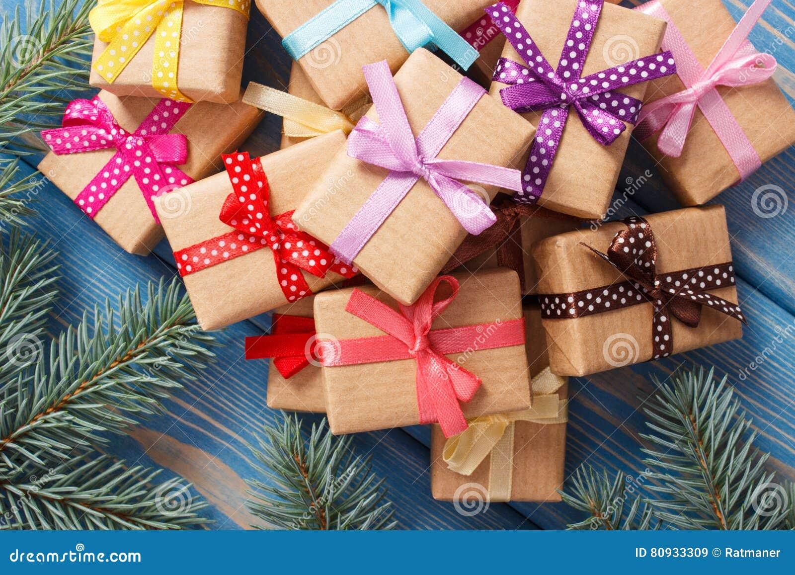 Τυλιγμένα δώρα με τις ζωηρόχρωμες κορδέλλες για τα Χριστούγεννα και τους κομψούς κλάδους
