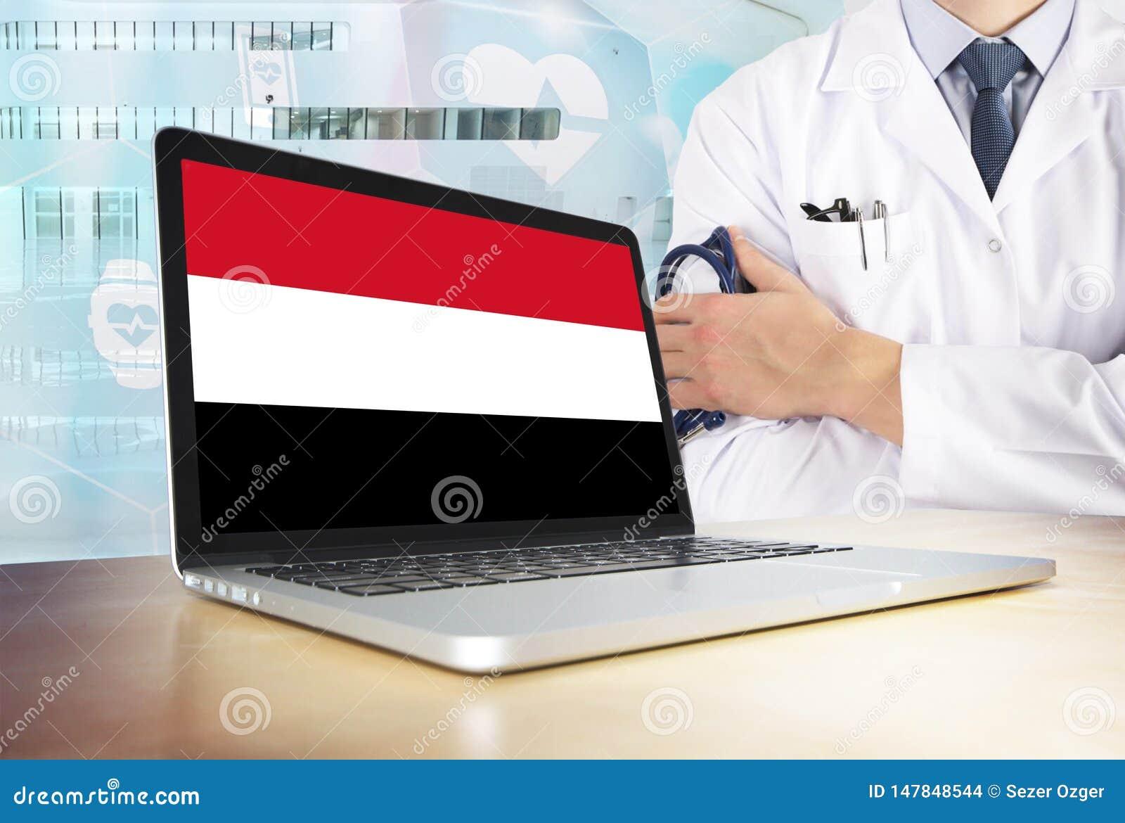Υγειονομικό σύστημα της Υεμένης στο θέμα τεχνολογίας Σημαία Γιεμενιτών στη οθόνη υπολογιστή Γιατρός που στέκεται με το στηθοσκόπι