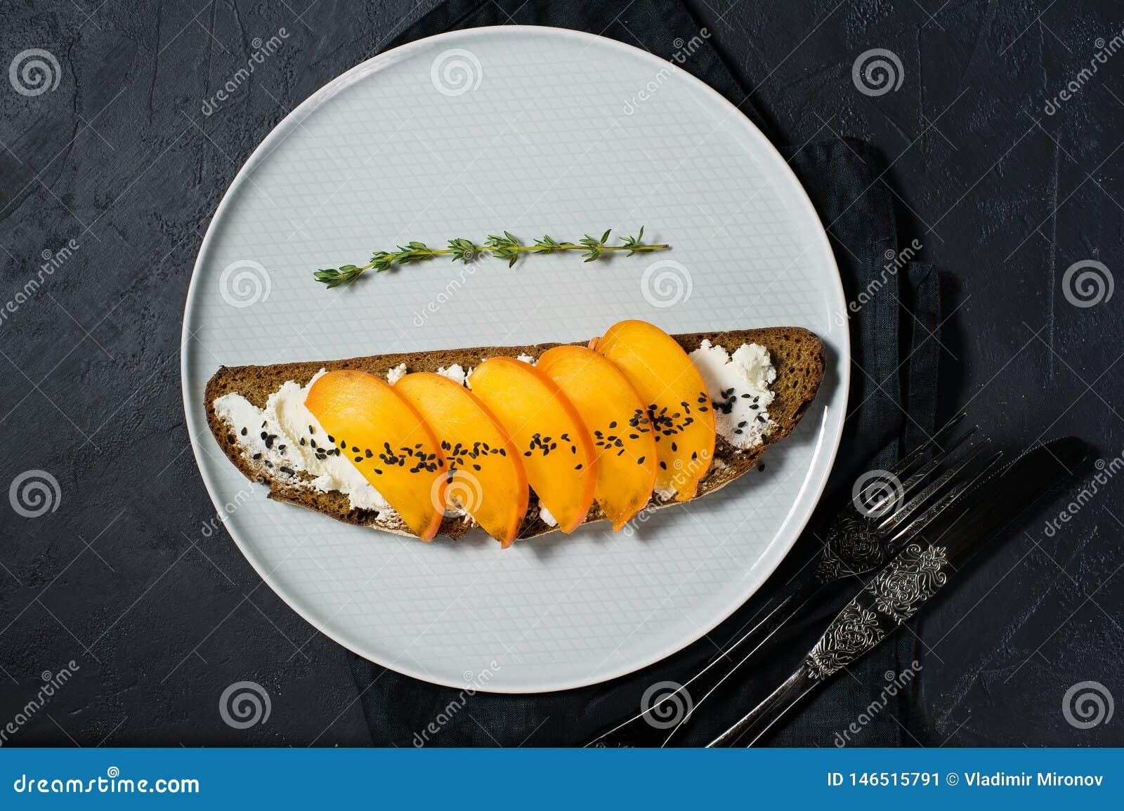 Υγιές ισορροπημένο σάντουιτς τροφίμων με persimmon και μαλακό τυρί στο μαύρο υπόβαθρο