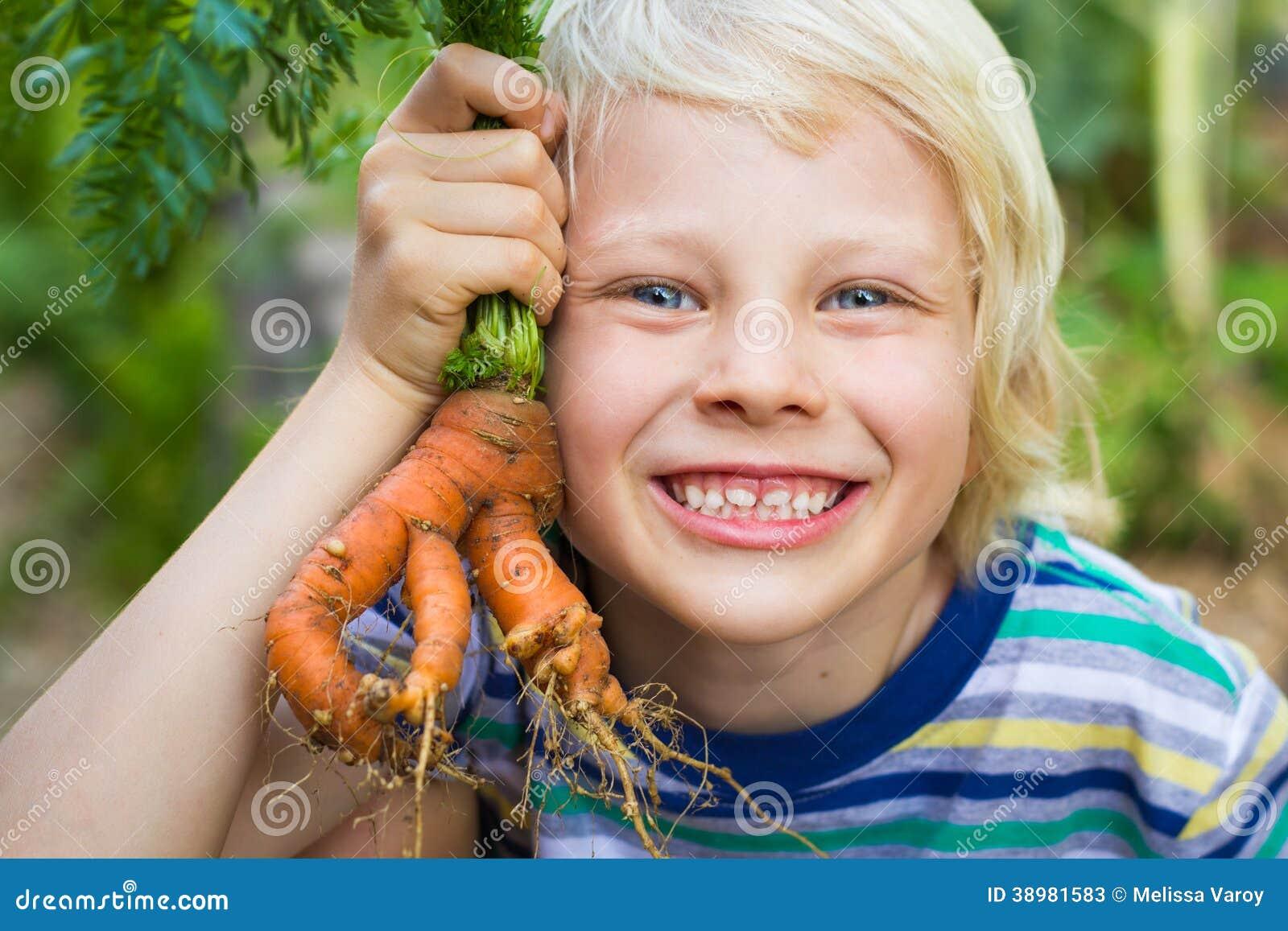 Υγιές παιδί στον κήπο που κρατά ένα ασυνήθιστο homegrown καρότο