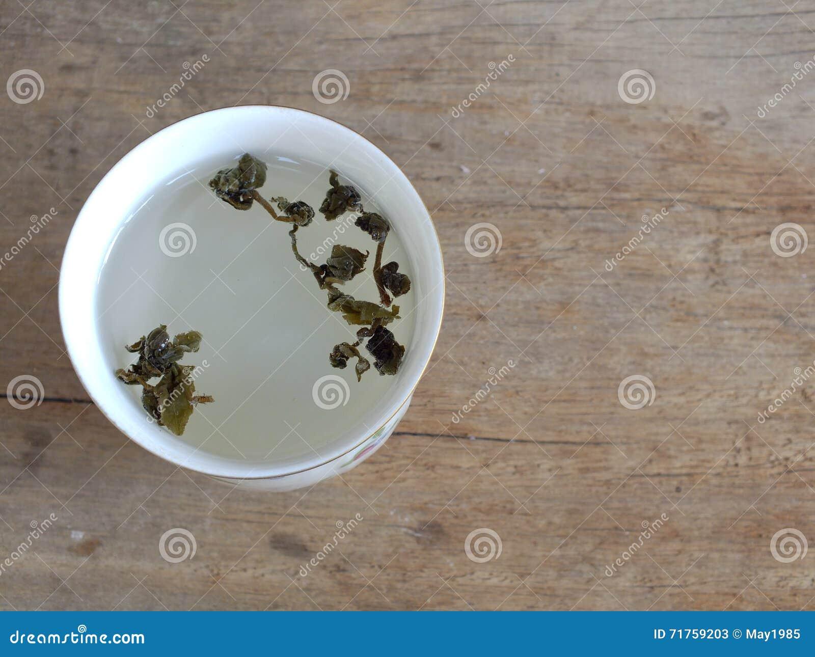 Υγιές πράσινο φλυτζάνι τσαγιού με τα φύλλα τσαγιού