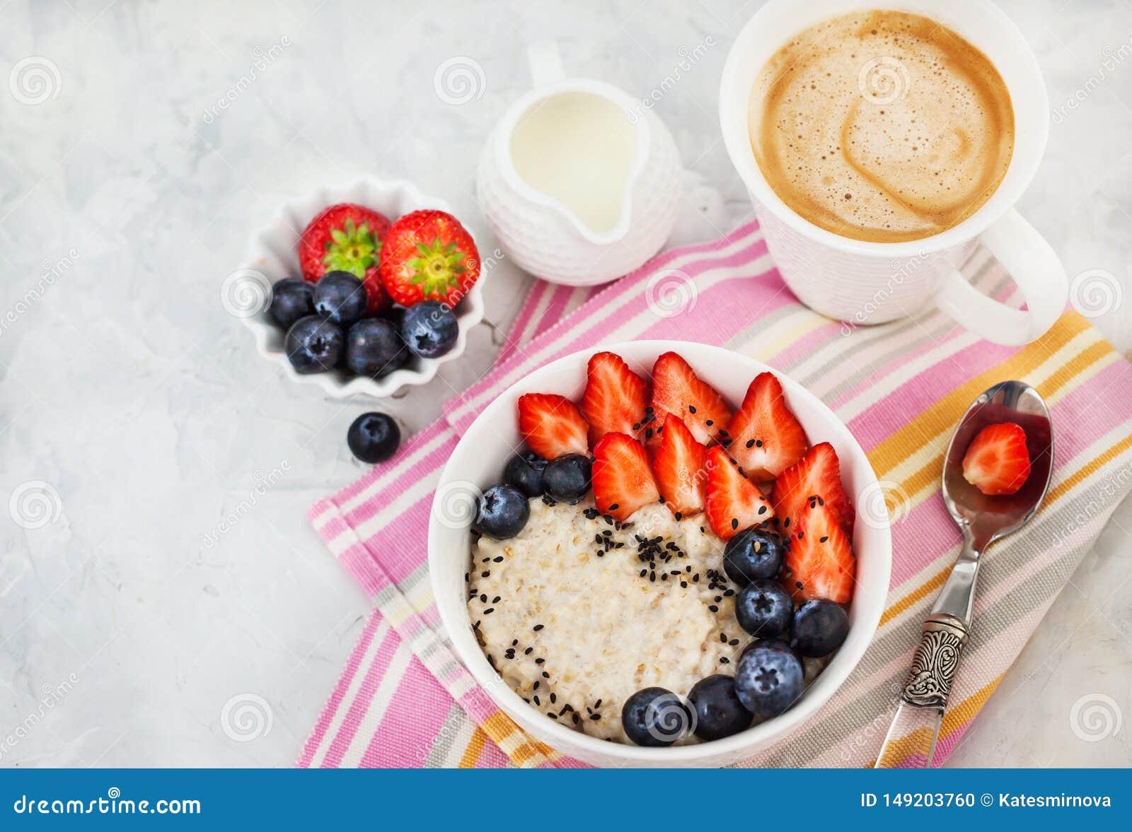 Υγιές πρόγευμα με oatmeal το κουάκερ, τα φρέσκους μούρα και τον καφέ