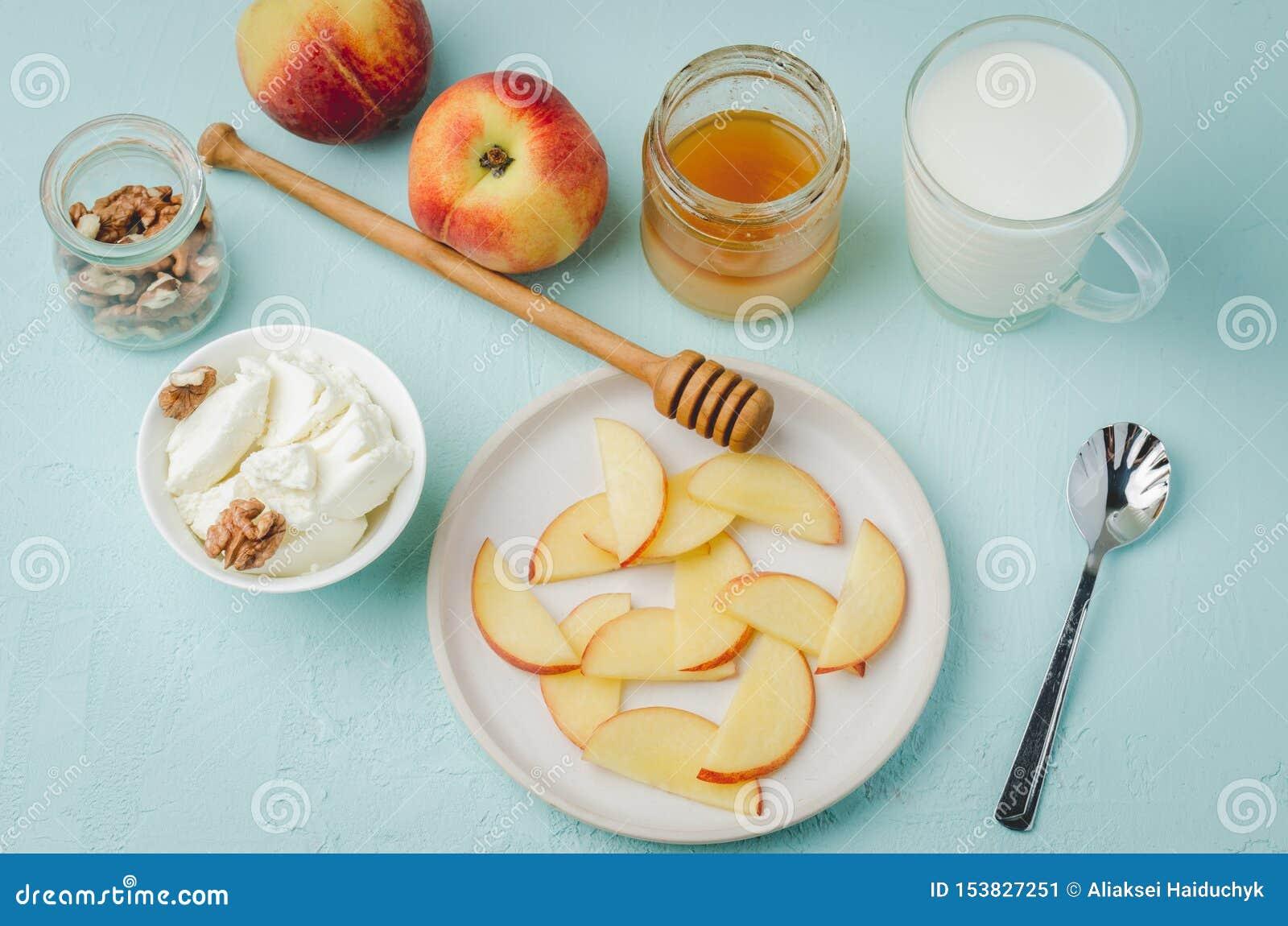 Υγιές υπόβαθρο προγευμάτων Ροδάκινο, μέλι, γάλα, τυρί εξοχικών σπιτιών και ξύλο καρυδιάς σε έναν μπλε πίνακα r