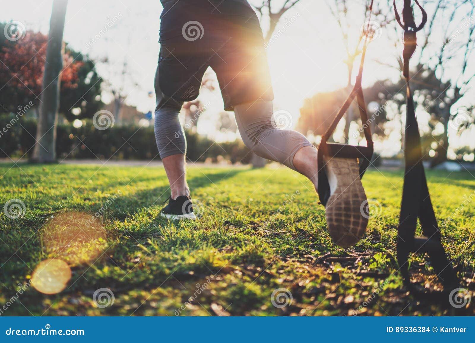 υγιής τρόπος ζωής έννοιας Μυϊκός αθλητής που ασκεί trx έξω στο ηλιόλουστο πάρκο Μεγάλο TRX workout Νέο όμορφο άτομο μέσα