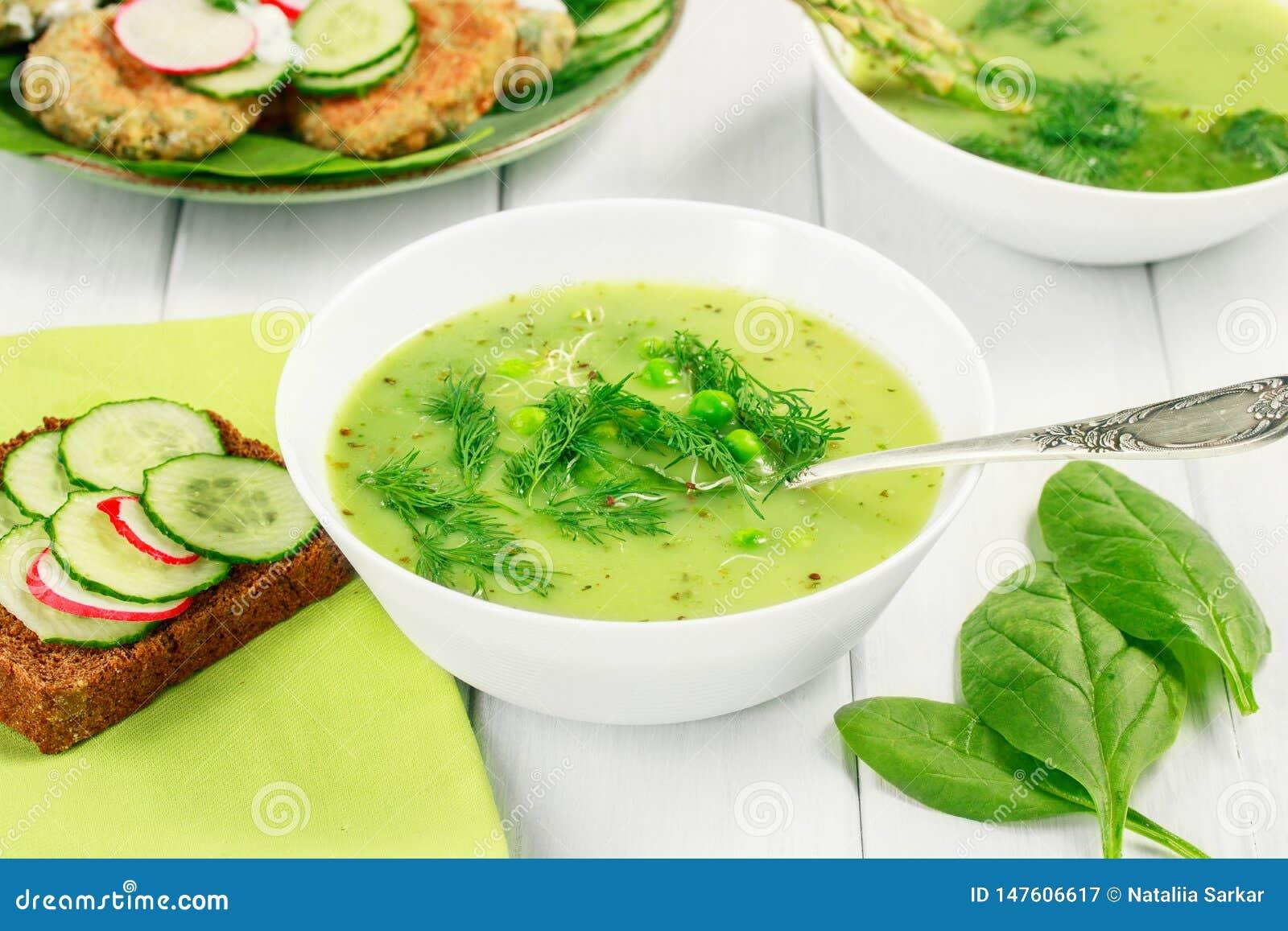 Υγιής χορτοφάγος σούπα τροφίμων με το σπαράγγι και το σπανάκι, πράσινα μπιζέλια και ψωμί με τα λαχανικά