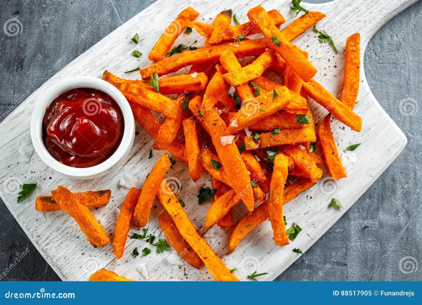 Υγιή σπιτικά ψημένα πορτοκαλιά τηγανητά γλυκών πατατών με το κέτσαπ, άλας, πιπέρι στο λευκό ξύλινο πίνακα