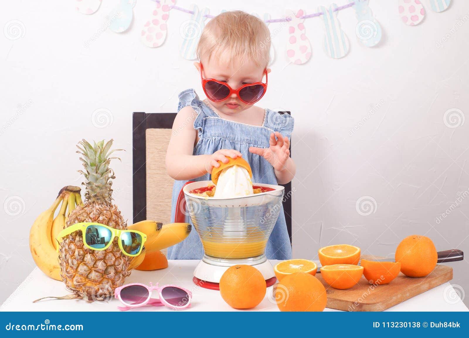 Υγιή τρόφιμα: Ένα μικρό κορίτσι κάνει το φρέσκο χυμό από πορτοκάλι