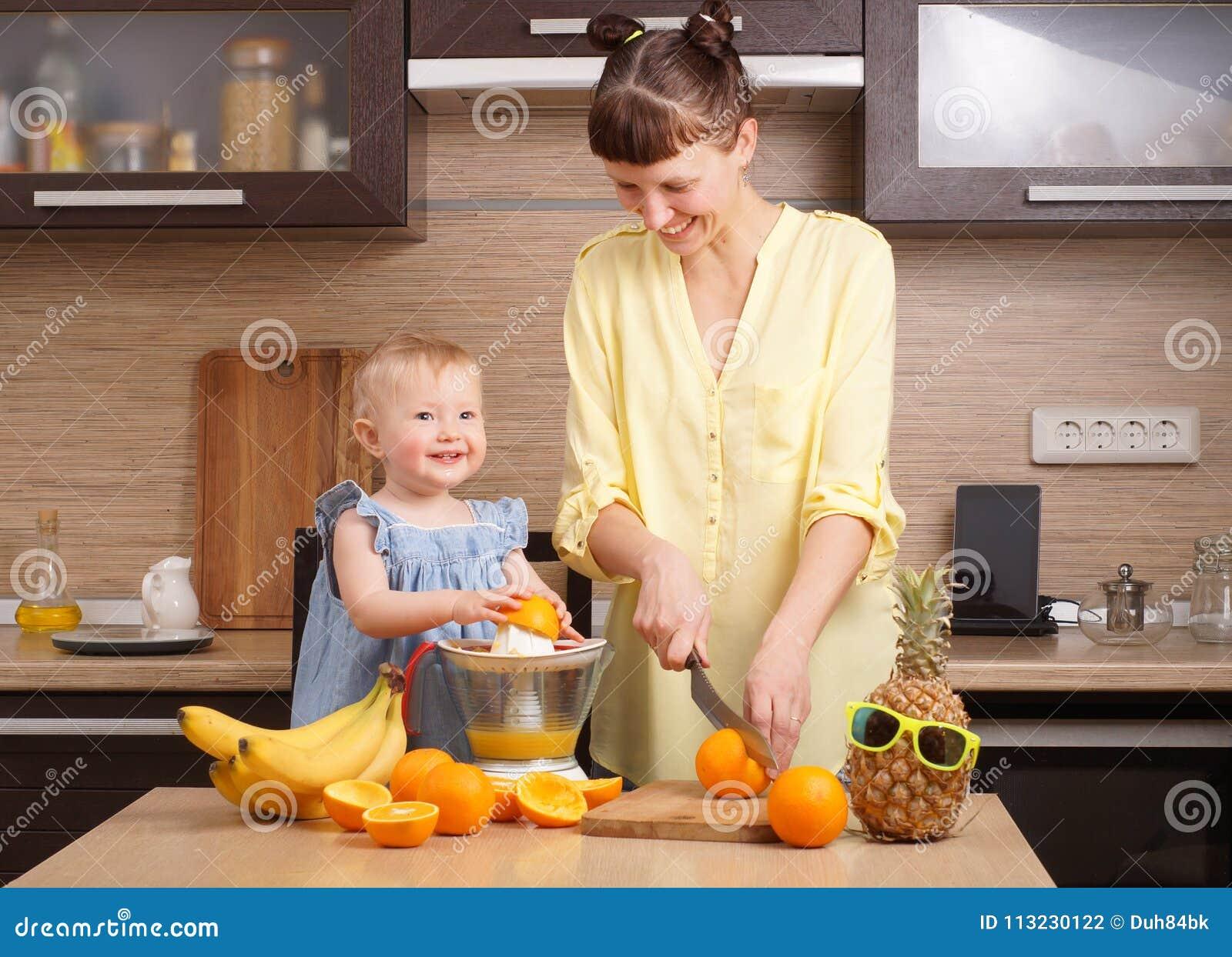Υγιή τρόφιμα για τα παιδιά: Το Mom και η κόρη κάνουν το φρέσκο χυμό από πορτοκάλι