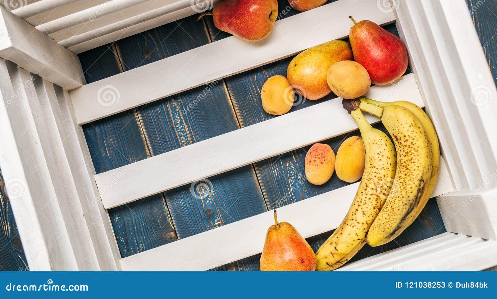 Υγιή τρόφιμα: Ώριμες φρέσκες μπανάνες, αχλάδια, βερίκοκα στο κατώτατο σημείο ενός ξύλινου κιβωτίου