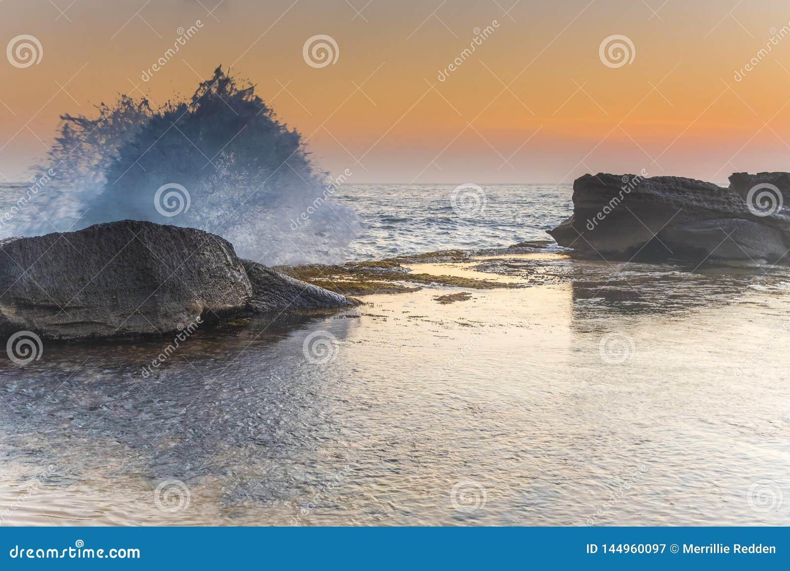 Υγρό Seascape με τους βράχους στο μαλακό πορτοκάλι