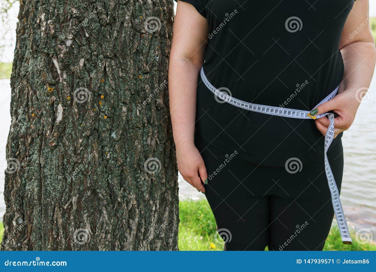 Υπέρβαρη στάση γυναικών που τυλίγεται με την ταινία μέτρου