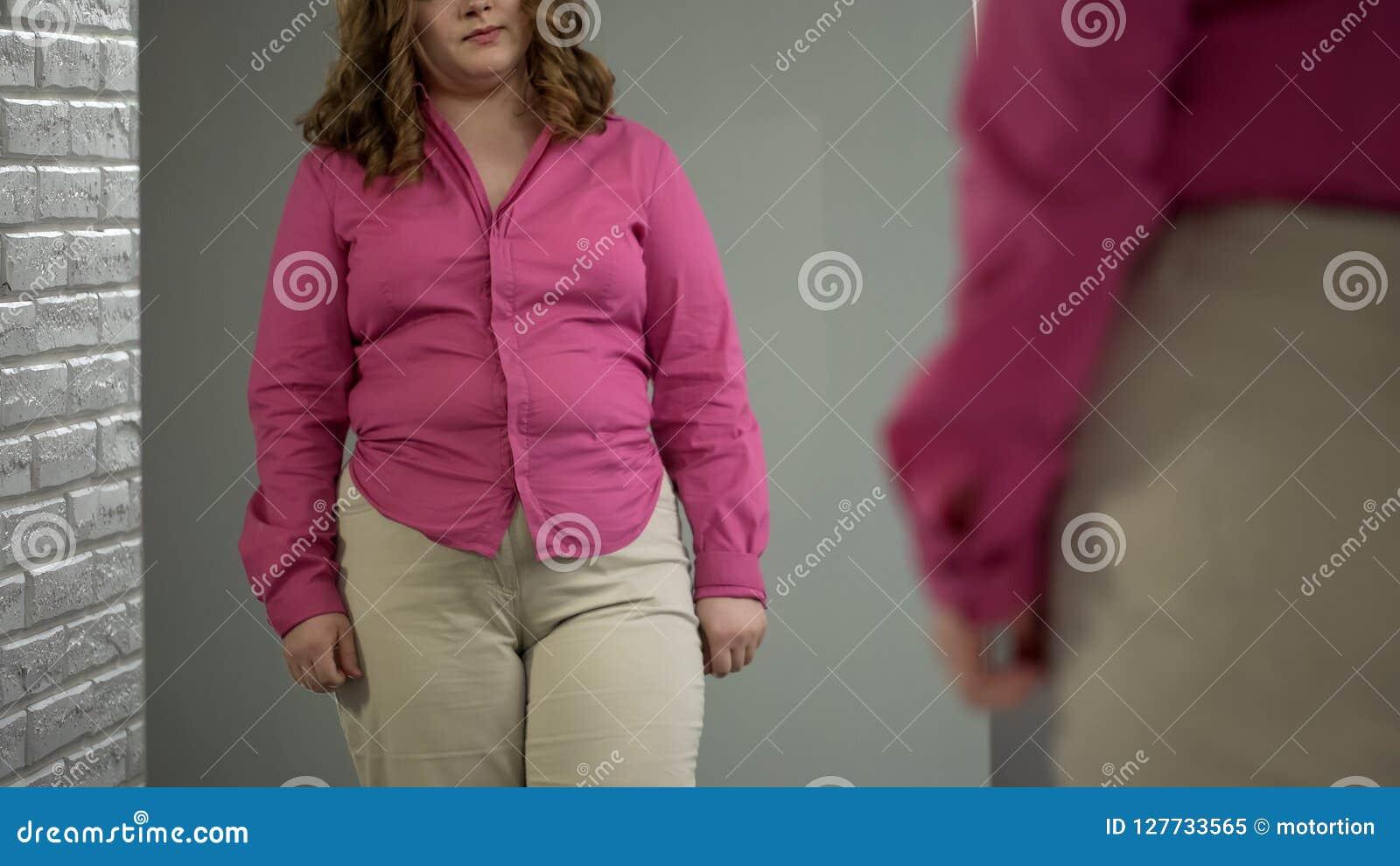 Υπέρβαρο θηλυκό που κοιτάζει στον καθρέφτη, που αξιολογεί την εμφάνισή της, πρόβλημα παχυσαρκίας