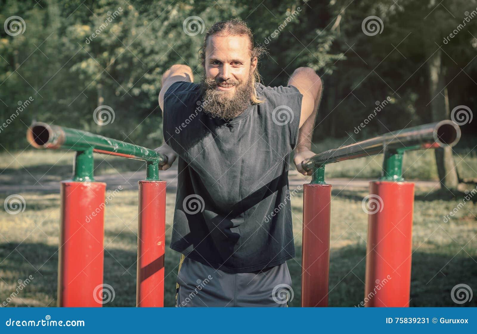 υπαίθρια εκπαιδευτικός Άτομο που κάνει τους δικέφαλους μυς και triceps την κατάρτιση εμβυθίσεων