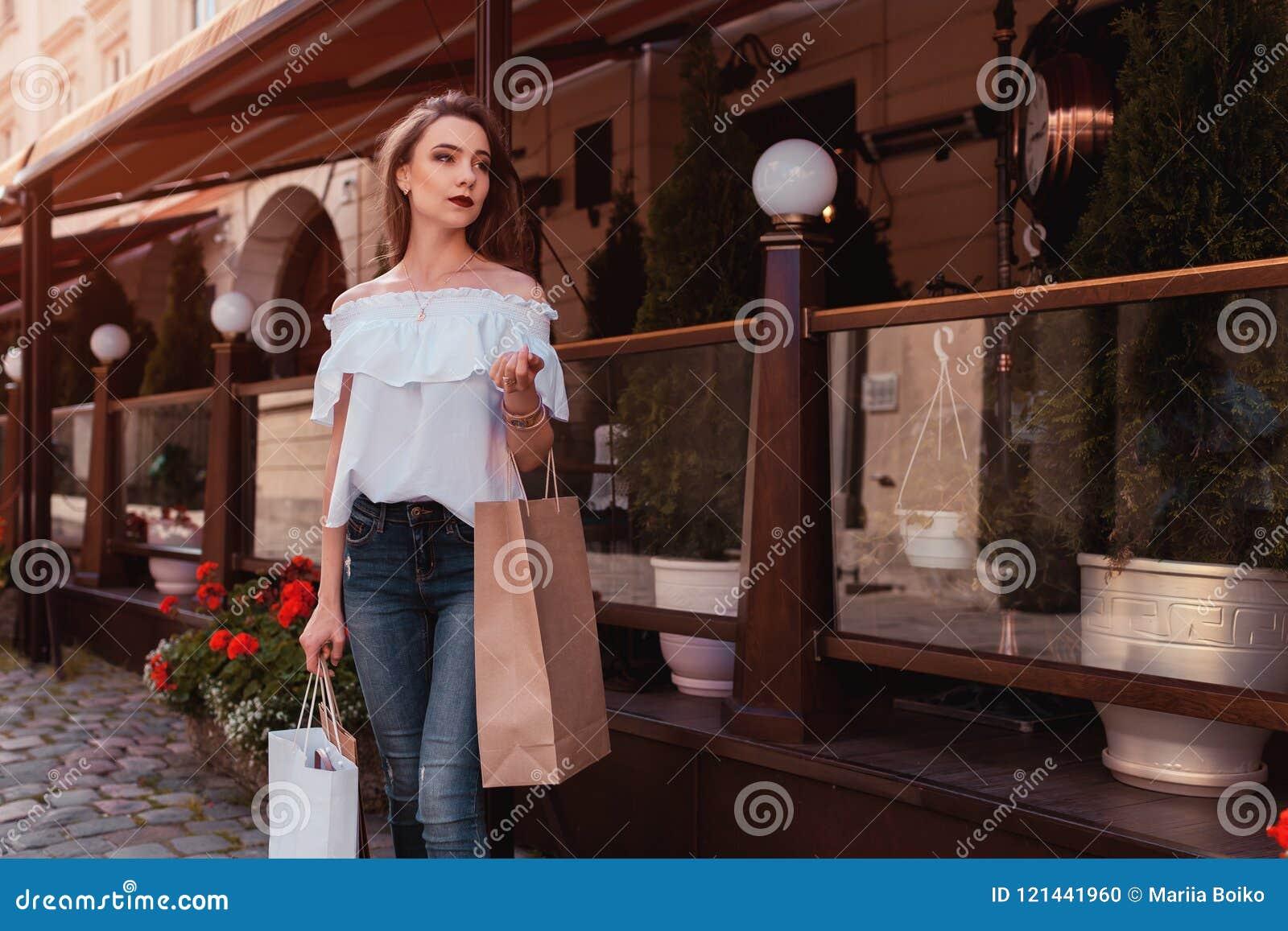 Υπαίθριο πορτρέτο του όμορφου μοντέρνου περπατήματος γυναικών στην οδό Πρότυπη αναμονή μόδας για τους φίλους από τον καφέ