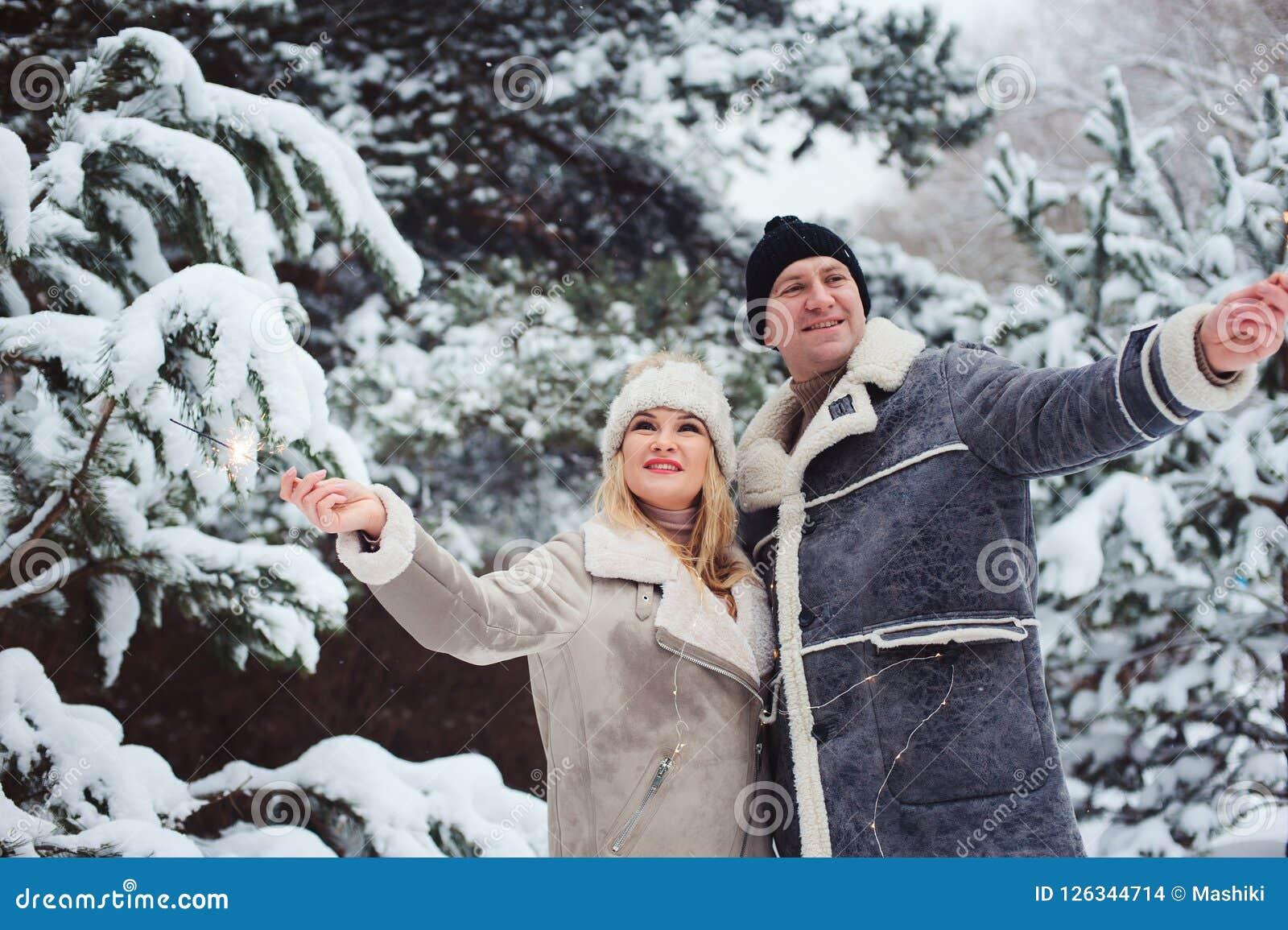 Υπαίθριο πορτρέτο των ευτυχών ρομαντικών Χριστουγέννων εορτασμού ζευγών με το κάψιμο των πυροτεχνημάτων στο χιονώδες δάσος