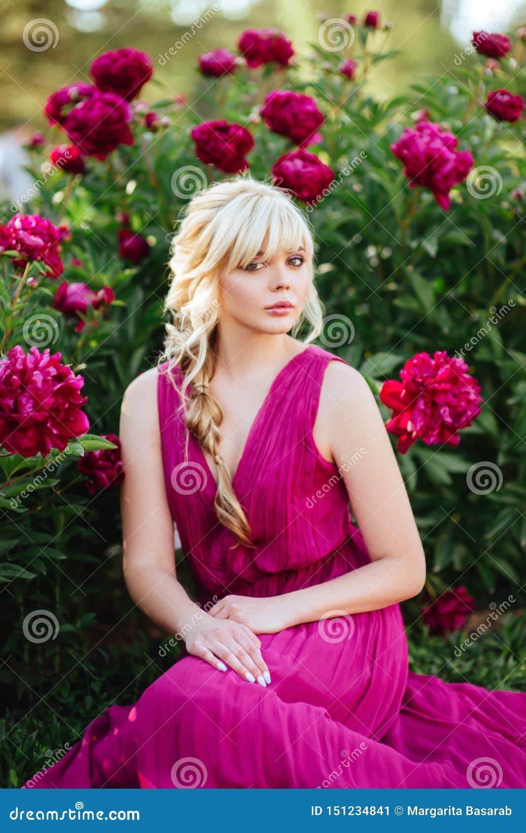 Υπαίθριο στενό επάνω πορτρέτο της όμορφης νέας γυναίκας στον ανθίζοντας κήπο Θηλυκή έννοια μόδας άνοιξη