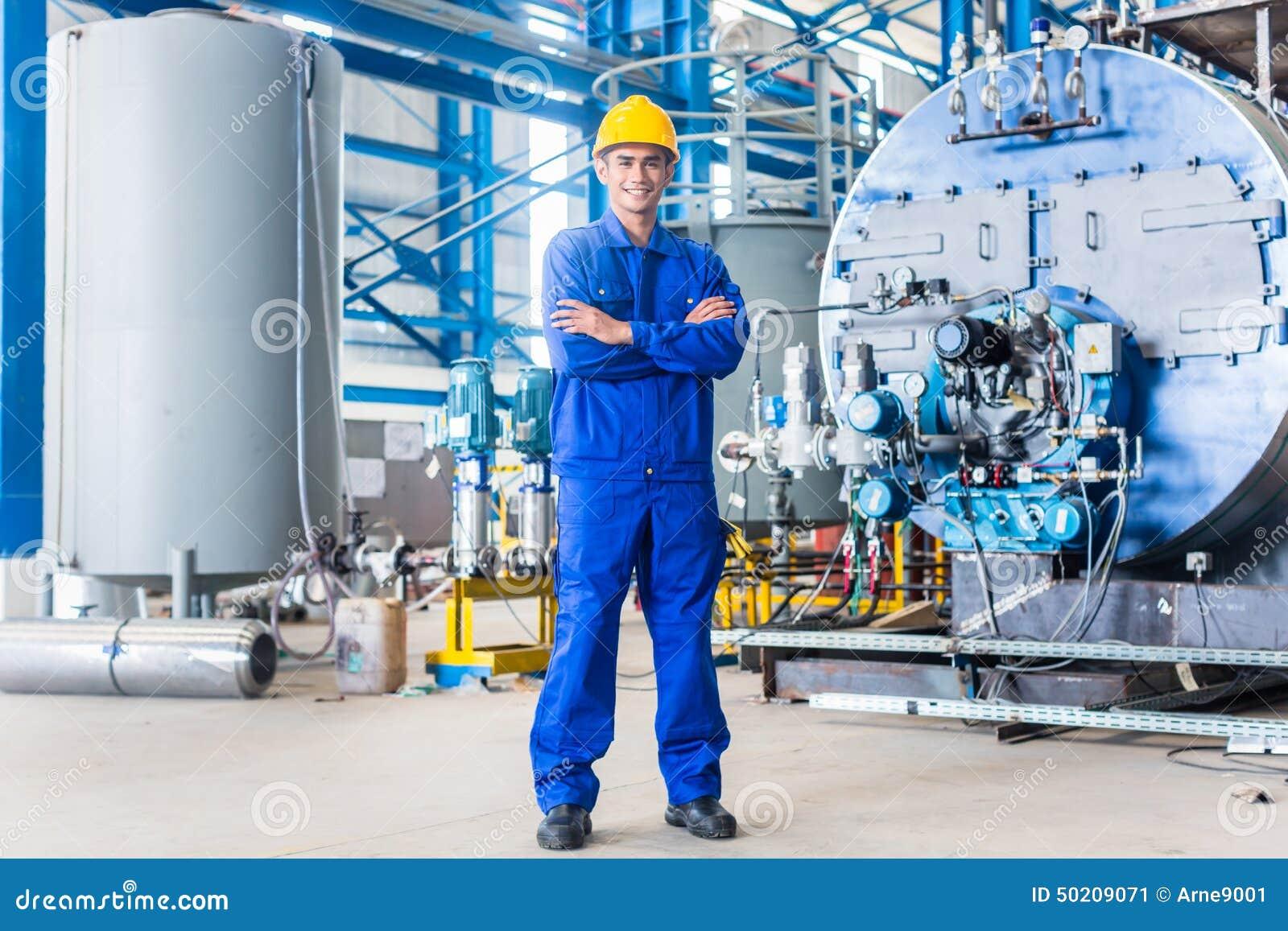 Υπερήφανος ασιατικός εργαζόμενος στο εργοστάσιο παραγωγής