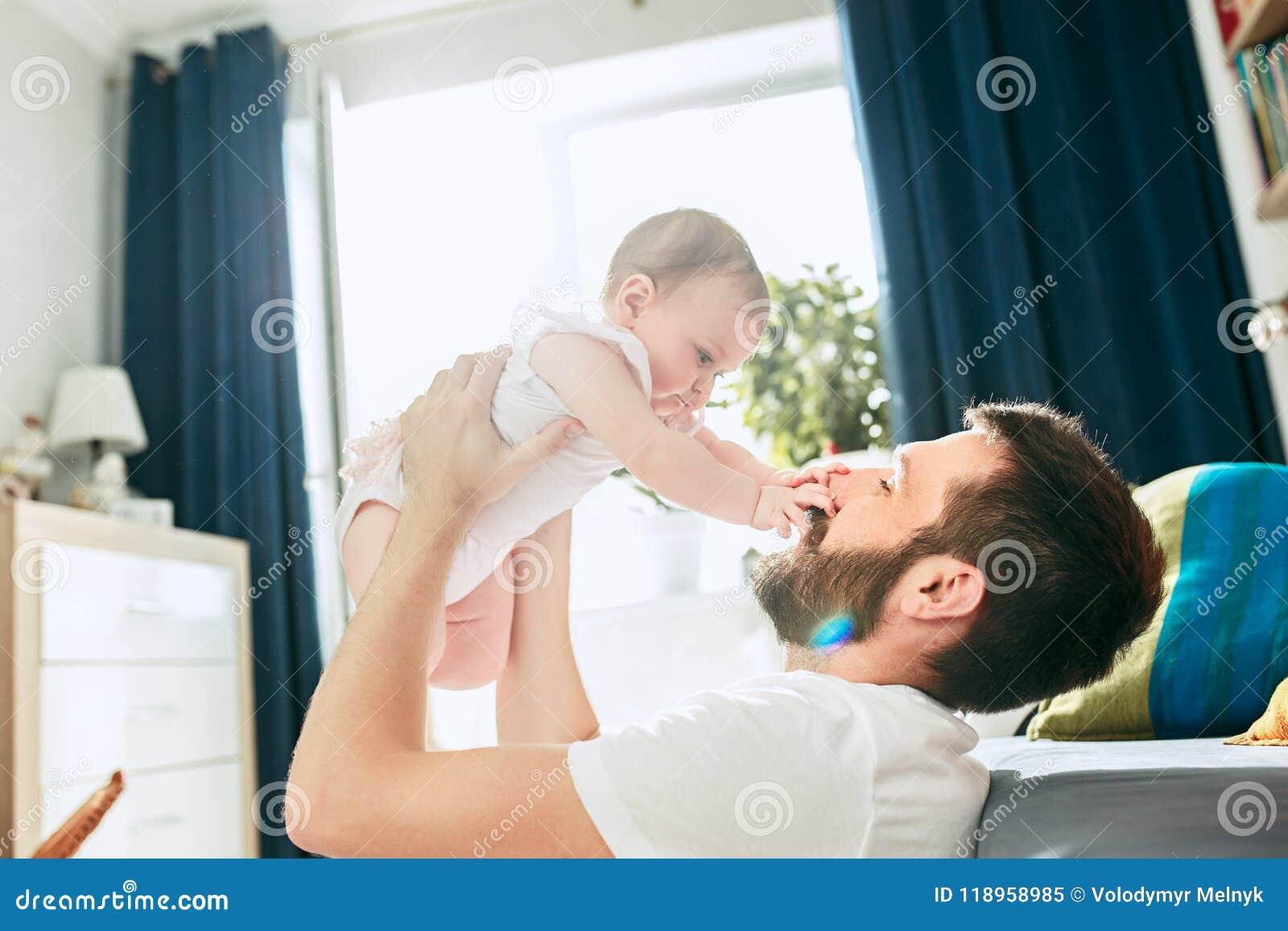 Υπερήφανος πατέρας που κρατά τη νεογέννητη κόρη μωρών του επάνω στον αέρα στο σπίτι