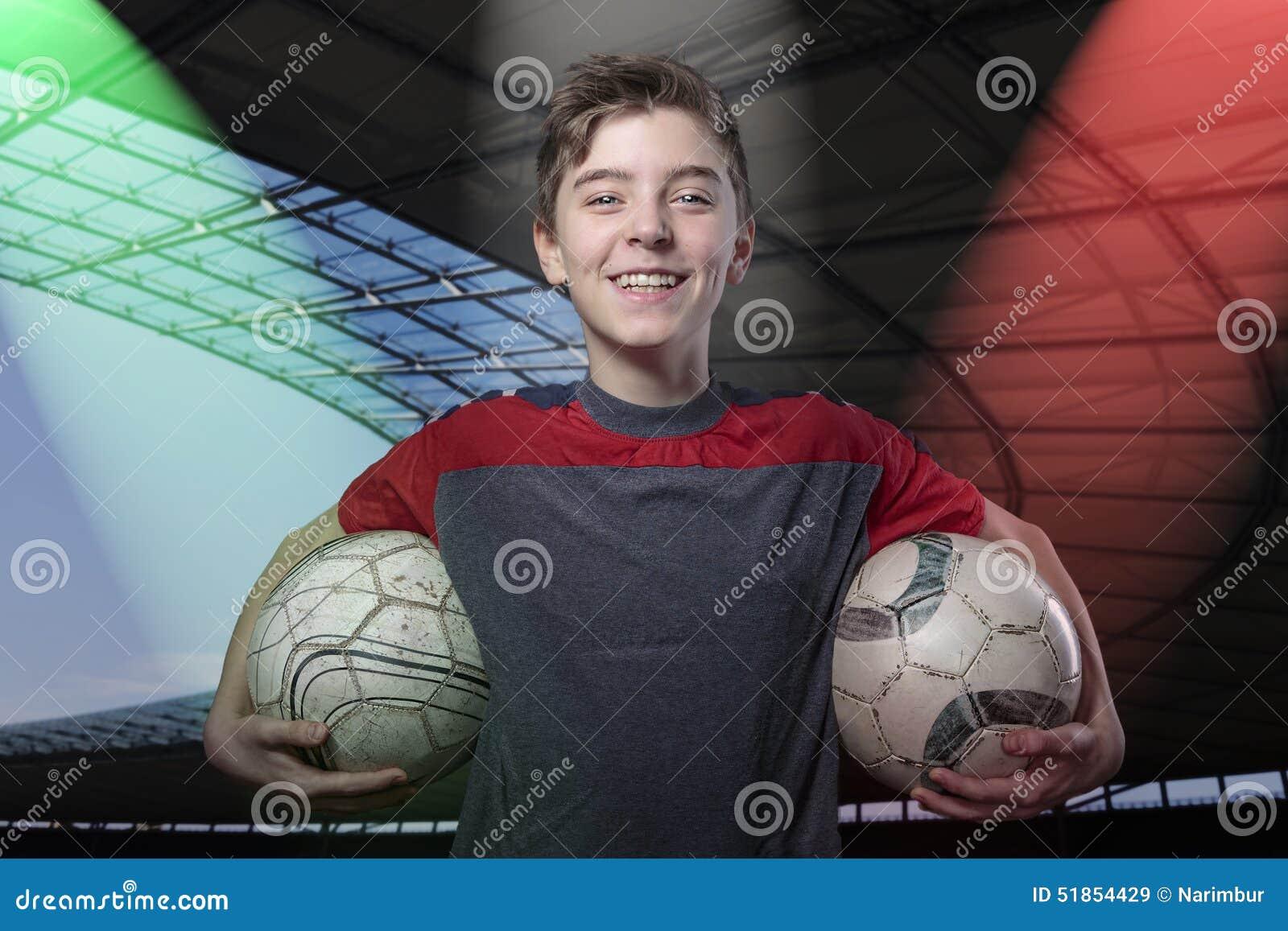 Υπερήφανος, χαμογελώντας έφηβος που κρατά της σφαίρας ποδοσφαίρου δύο