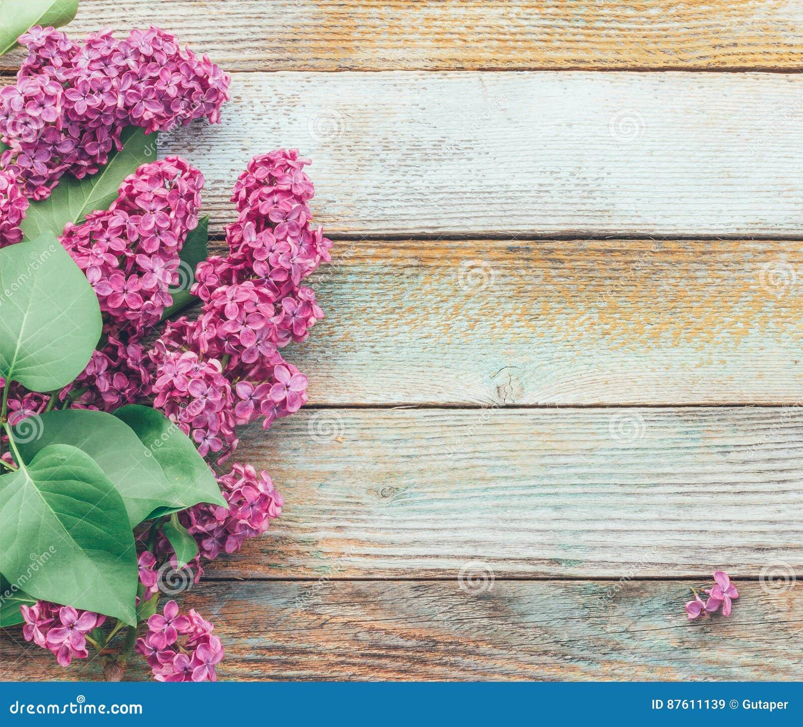 Υπόβαθρο άνοιξη με μια ανθοδέσμη των ιωδών λουλουδιών στην ξύλινη σανίδα
