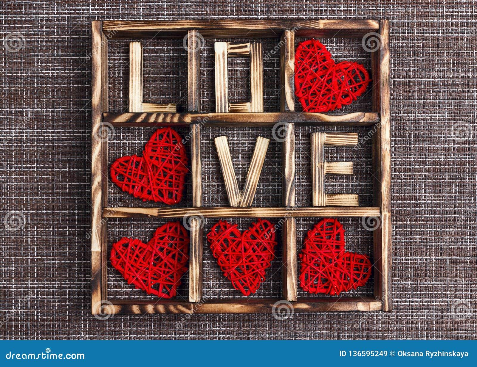 Υπόβαθρο ημέρας βαλεντίνου με την αγάπη και καρδιές στο ξύλινο κιβώτιο sackcloth