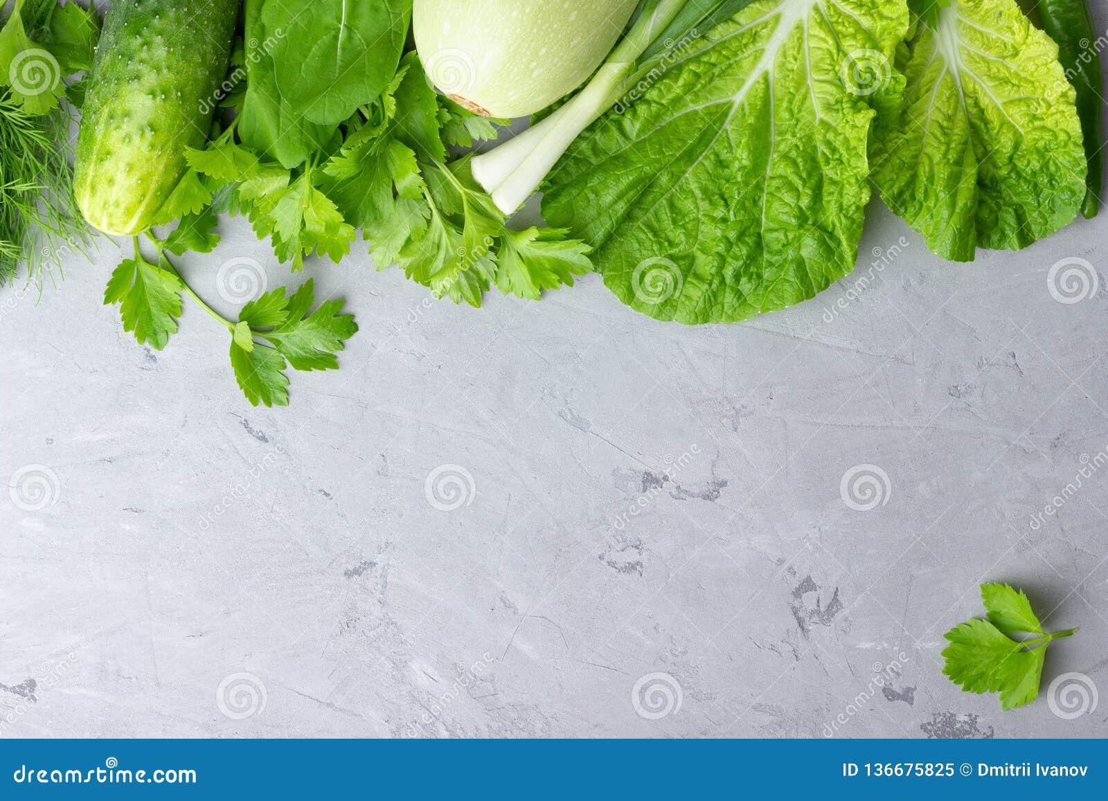 Υπόβαθρο με τα πράσινα λαχανικά, τη σαλάτα, το αγγούρι, το πράσινα κρεμμύδι και τα κολοκύθια στην γκρίζα επιτραπέζια κορυφή πετρώ