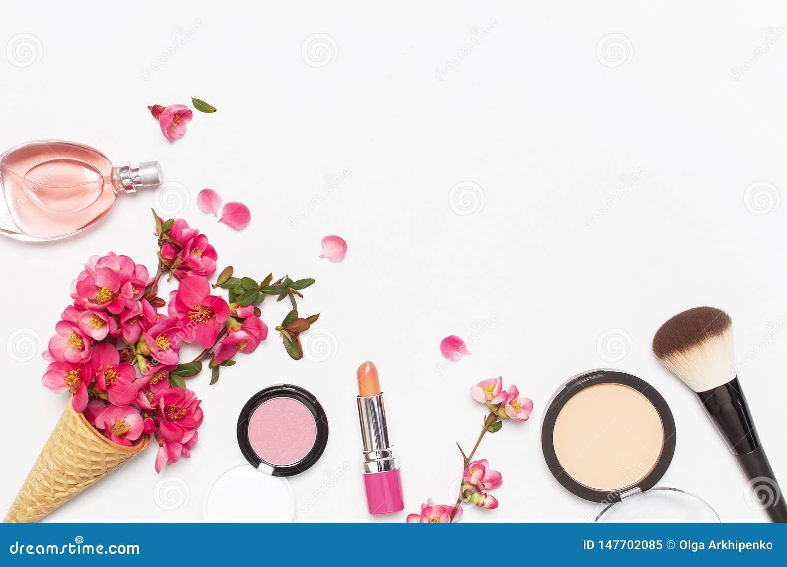 Υπόβαθρο ομορφιάς Ο κώνος βαφλών με το ρόδινο ελατήριο ανθίζει και διαφορετικό καλλυντικό makeup στο ελαφρύ υπόβαθρο Κραγιόν σκον