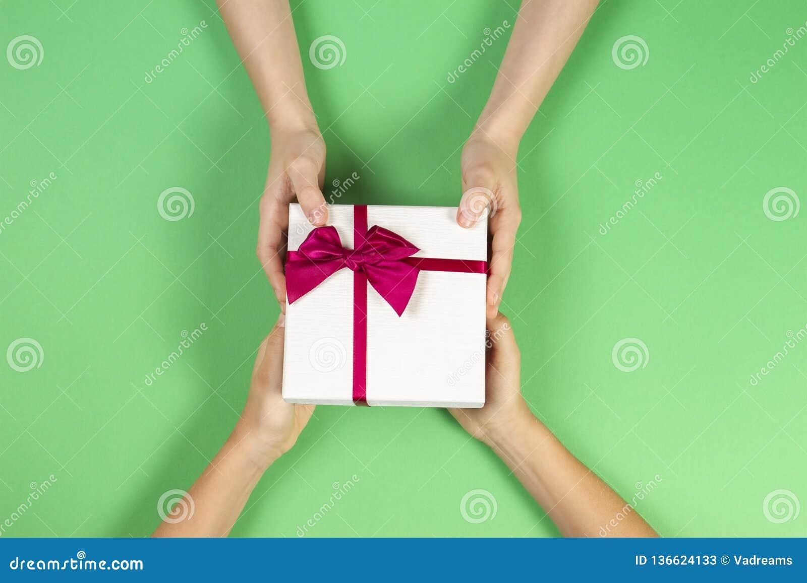 Υπόβαθρο συγχαρητηρίων Τοπ άποψη δύο χεριών προσώπων που δίνουν και που λαμβάνουν ένα παρόν κιβώτιο δώρων με την κορδέλλα σε πράσ