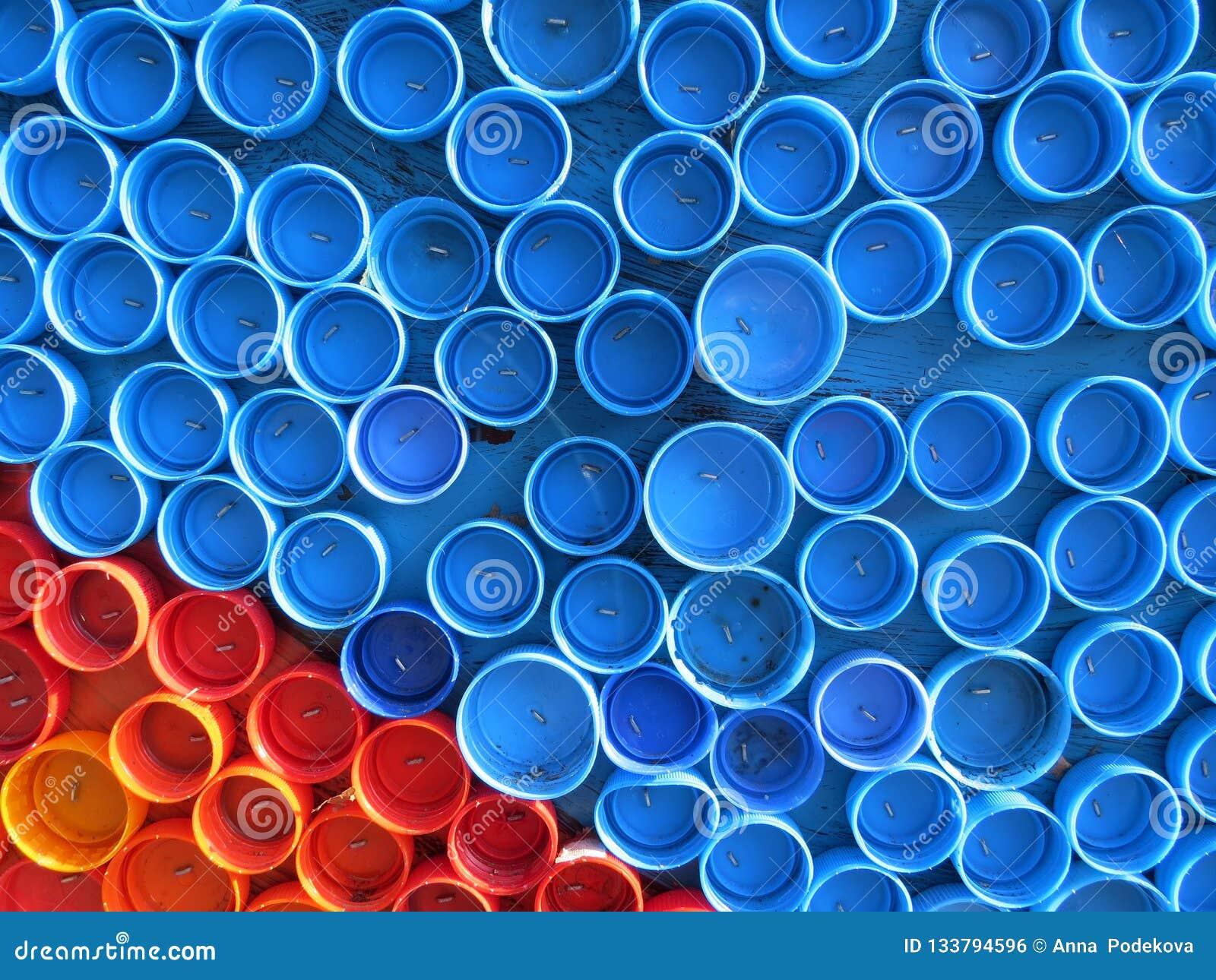 Υπόβαθρο των πλαστικών ζωηρόχρωμων καλυμμάτων μπουκαλιών Μόλυνση με τα πλαστικά απόβλητα Περιβάλλον και οικολογική ισορροπία Τέχν