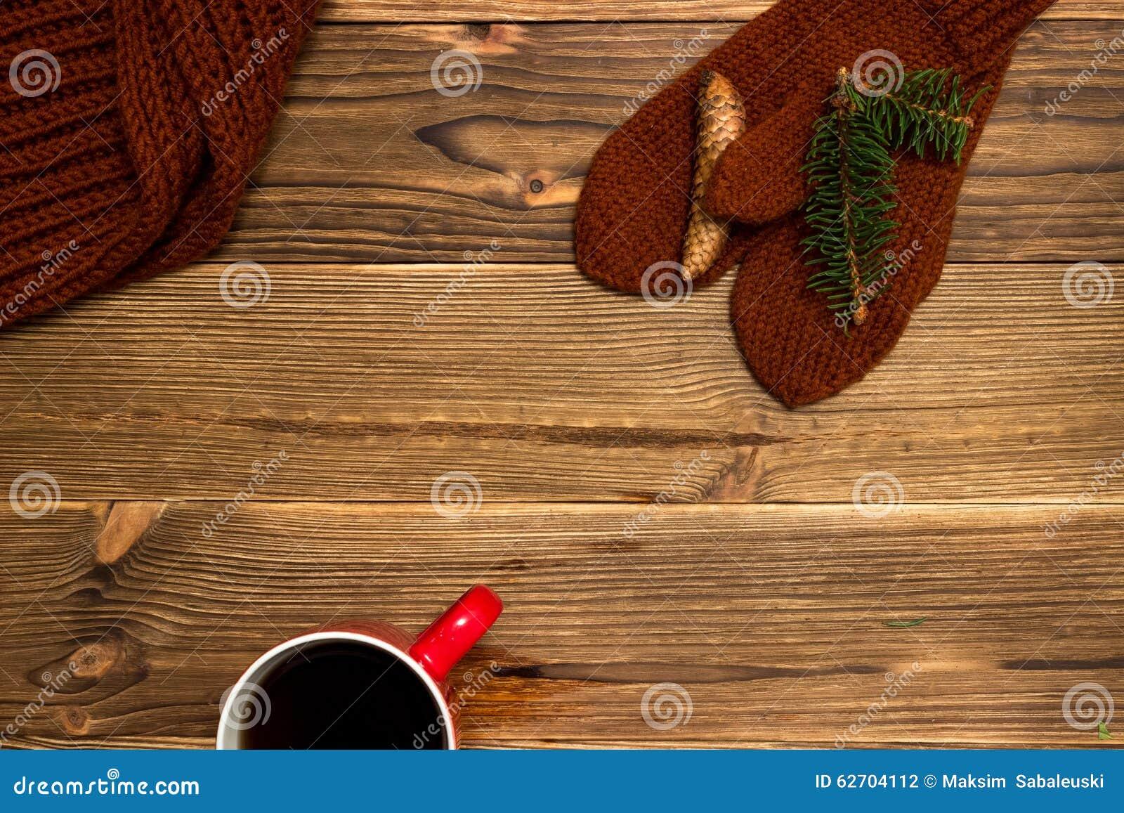 Υπόβαθρο Χριστουγέννων με τα πλεκτά γάντια και ένα φλιτζάνι του καφέ