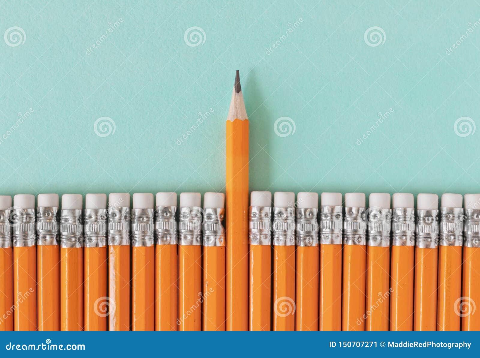 Υπόλοιπος κόσμος των πορτοκαλιών μολυβιών με ένα ακονισμένο μολύβι Ηγεσία/διαχωρισμός από μια έννοια πλήθους με το διάστημα αντιγ