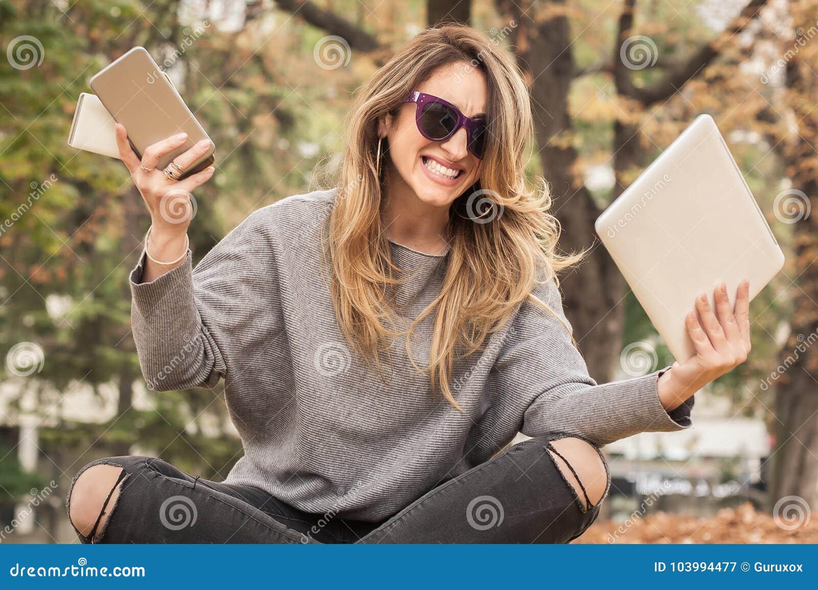 Υστερικό κορίτσι με πάρα πολλές οθόνες, mobils, ταμπλέτες και το lapto