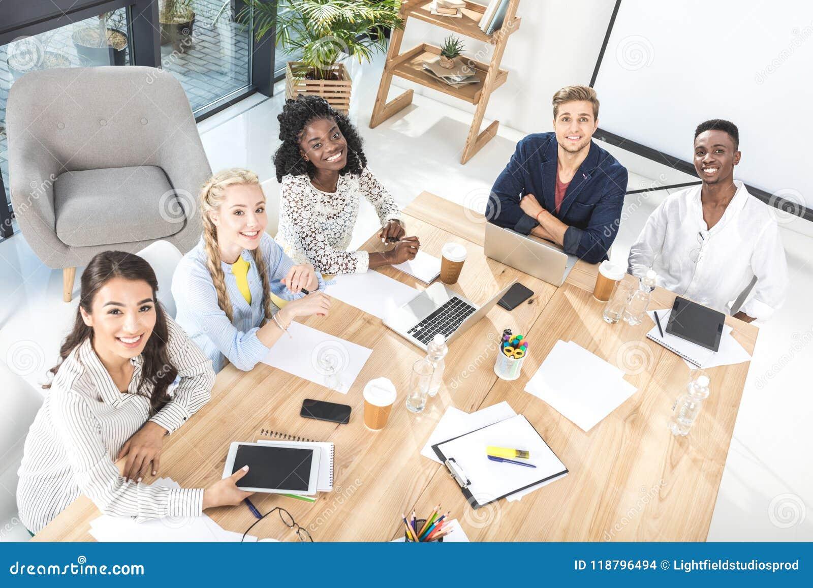 υψηλή άποψη γωνίας της πολυπολιτισμικής ομάδας επιχειρηματιών που εξετάζουν τη κάμερα καθμένος στον πίνακα