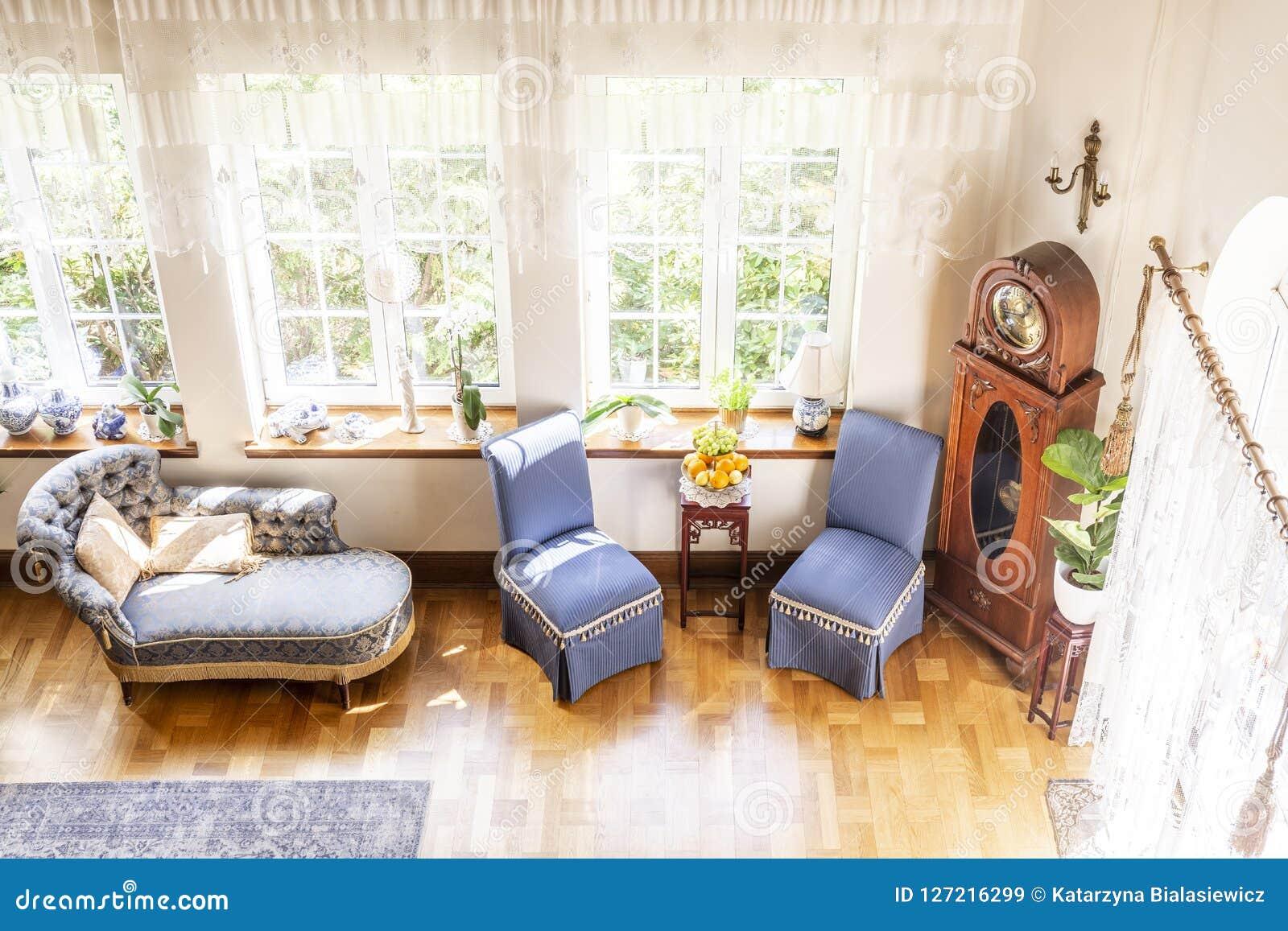 Υψηλή γωνία ενός ασημένιου σαλονιού, μπλε καρεκλών και ενός ξύλινου ρολογιού stan