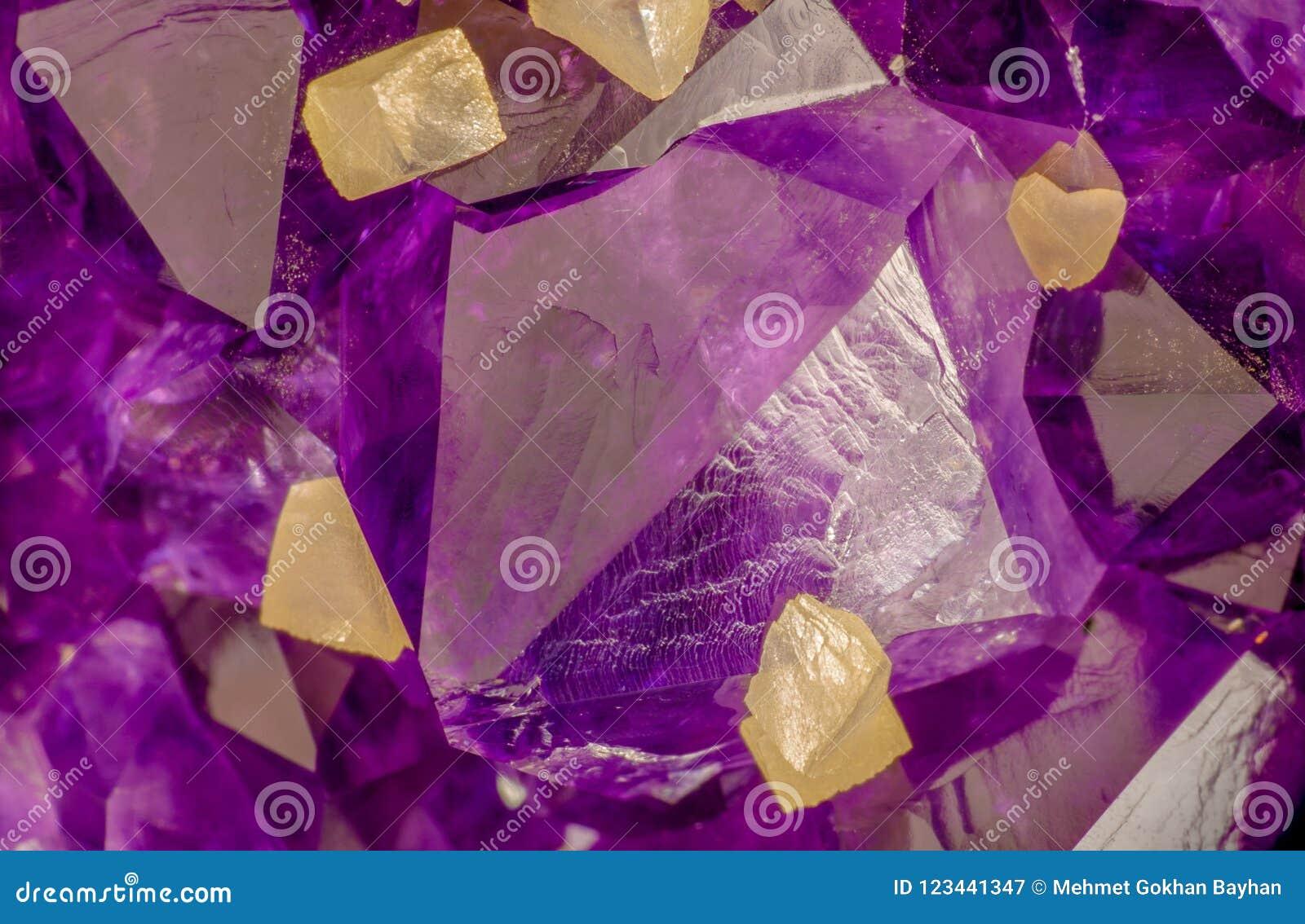 Υψηλή μακρο φωτογραφία ενίσχυσης των αμεθύστινων κρυστάλλων με τους κίτρινους calcite κύβους