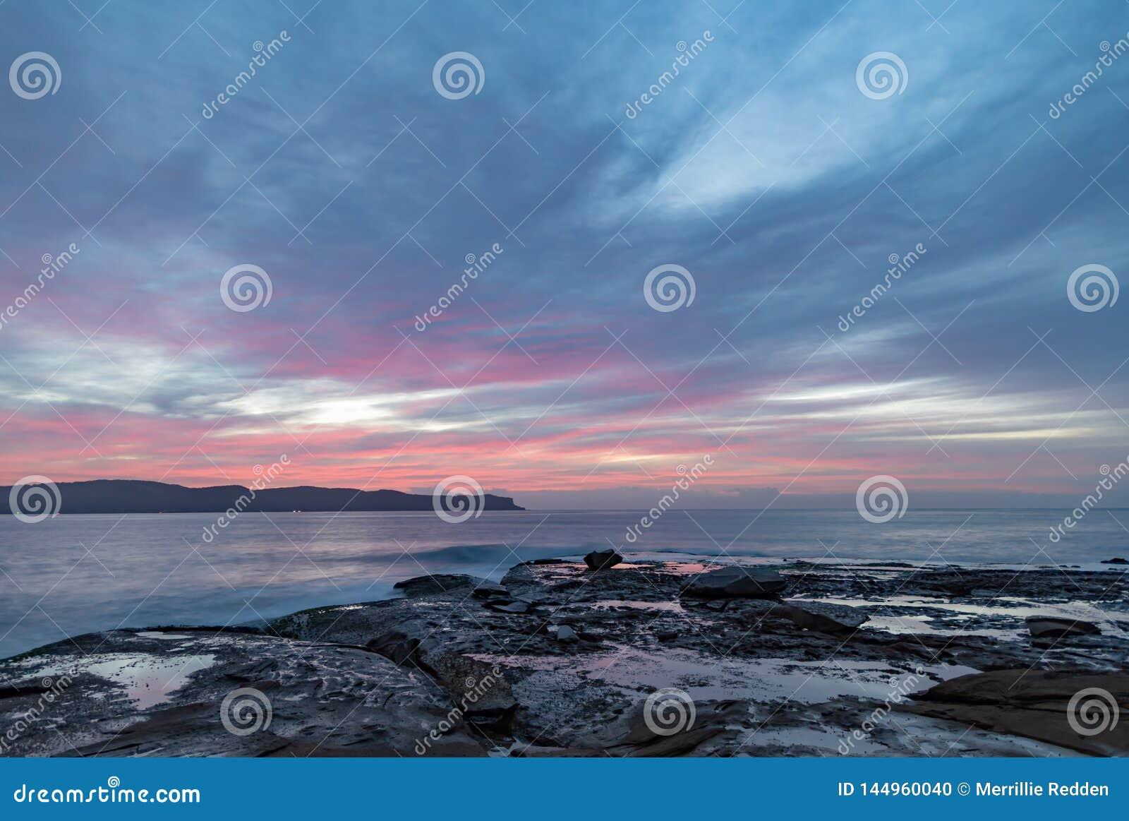 Υψηλό σύννεφο η ρόδινη Dawn Seascape από την πλατφόρμα βράχου