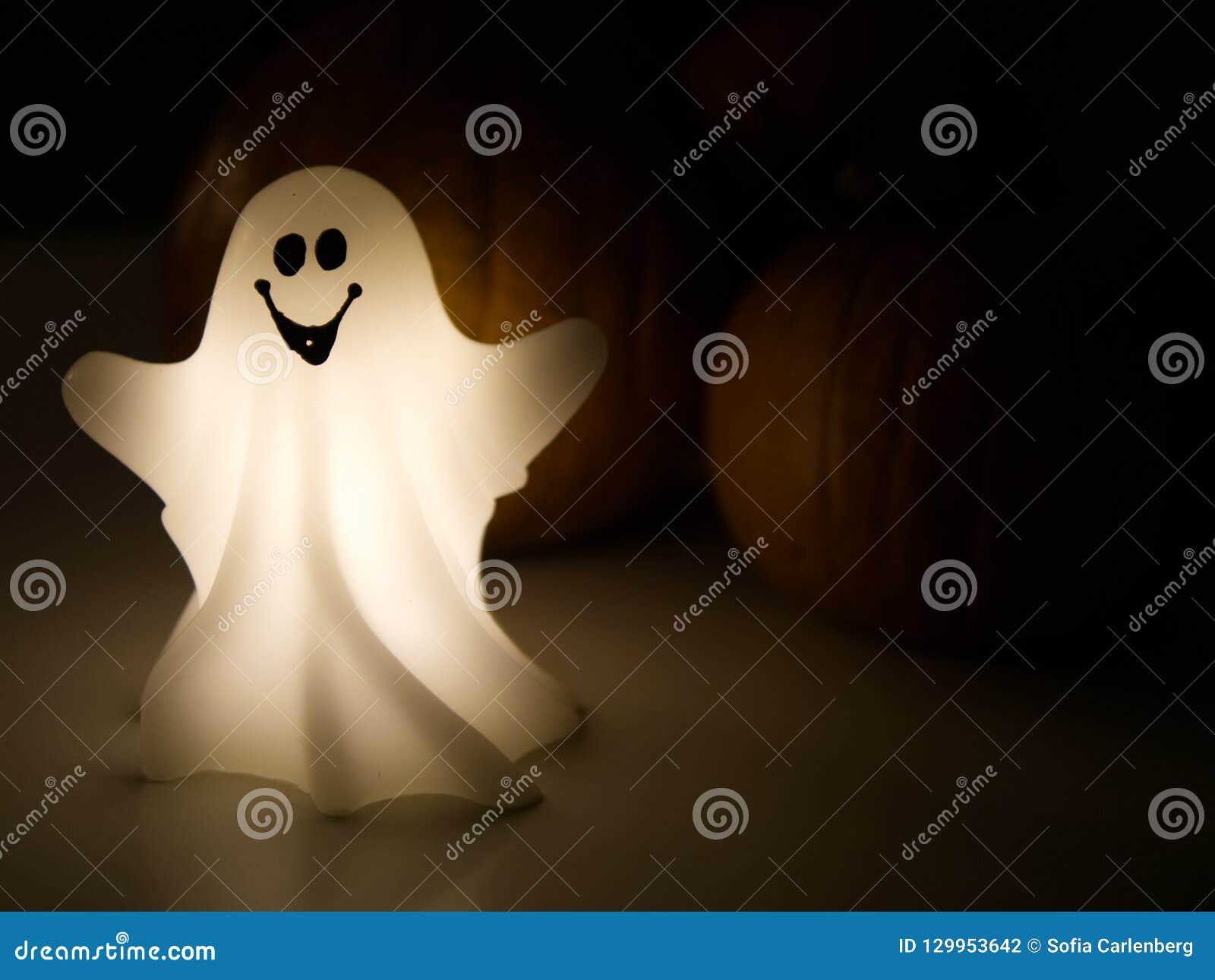 Φάντασμα αποκριών με τις κολοκύθες το σκοτεινό υπόβαθρο