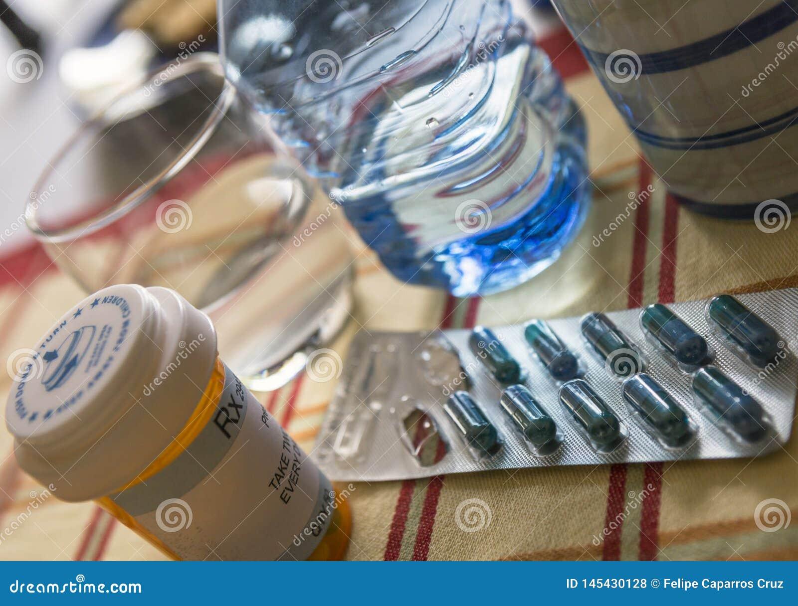 Φάρμακο κατά τη διάρκεια του προγεύματος, κάψες δίπλα σε ένα ποτήρι του νερού, εννοιολογική εικόνα