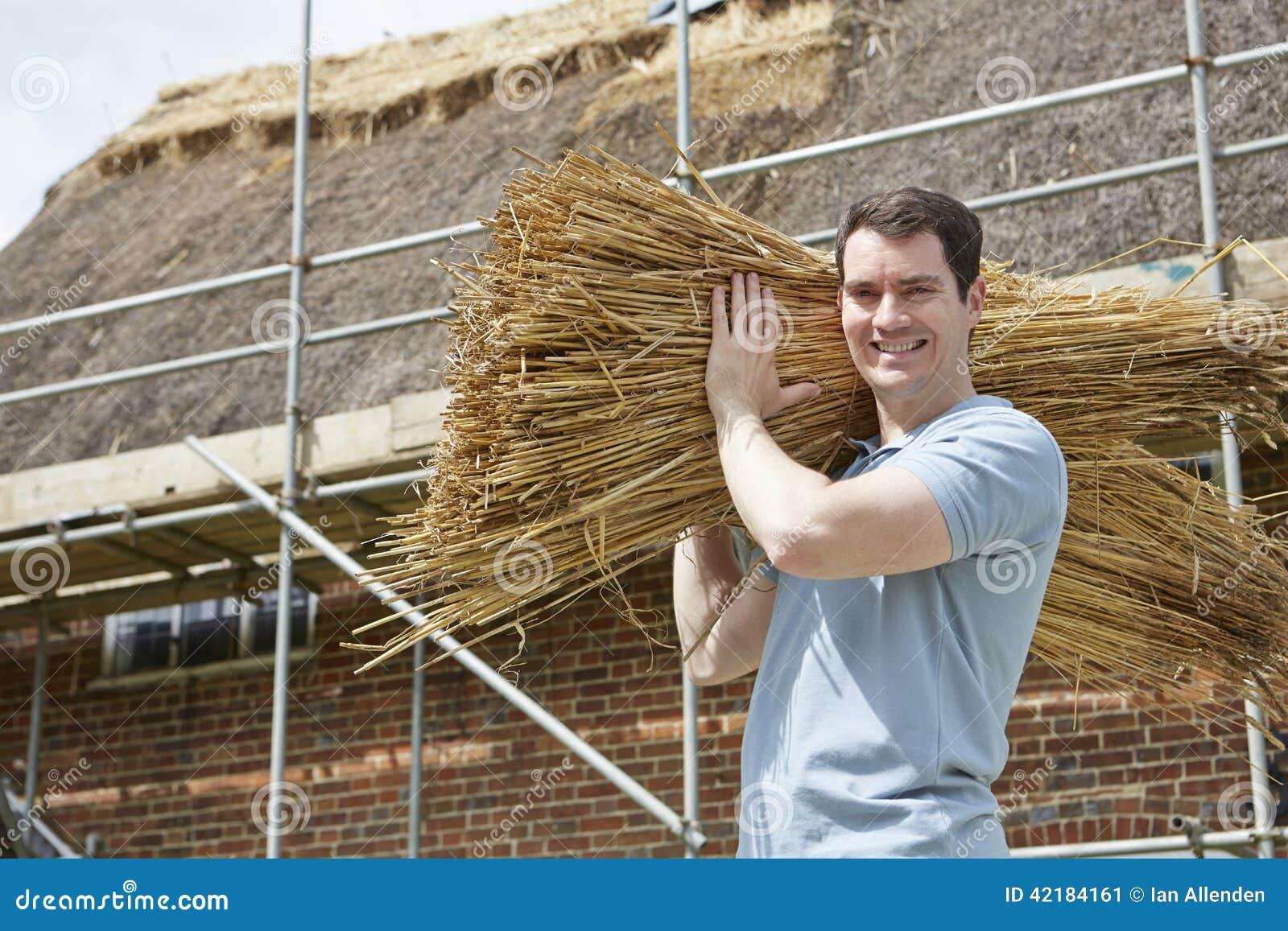Φέρνοντας δέσμες της Θάτσερ των καλάμων που λειτουργούν στη στέγη