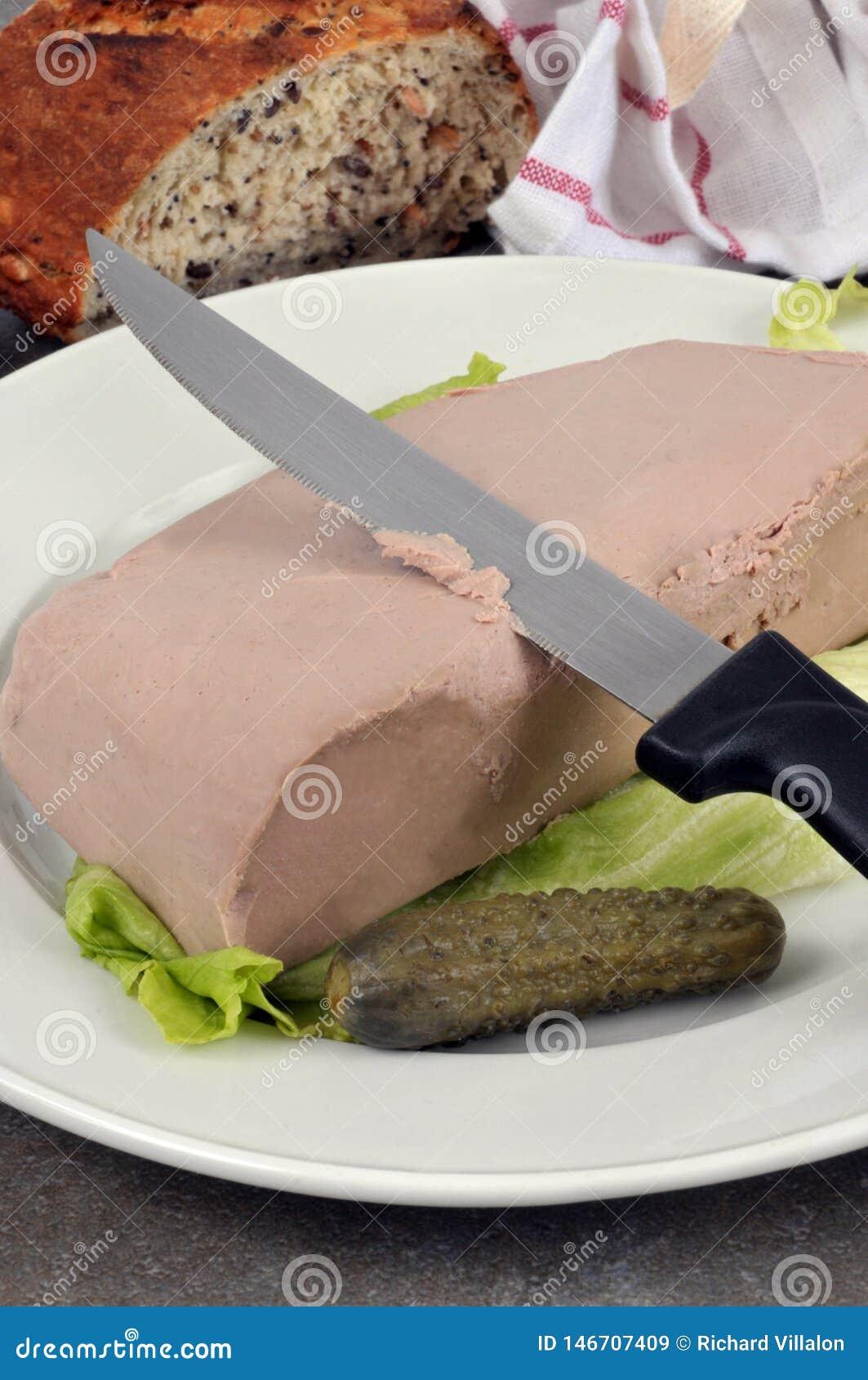 Φέτα του πατέ συκωτιού με ένα τουρσί σε ένα πιάτο
