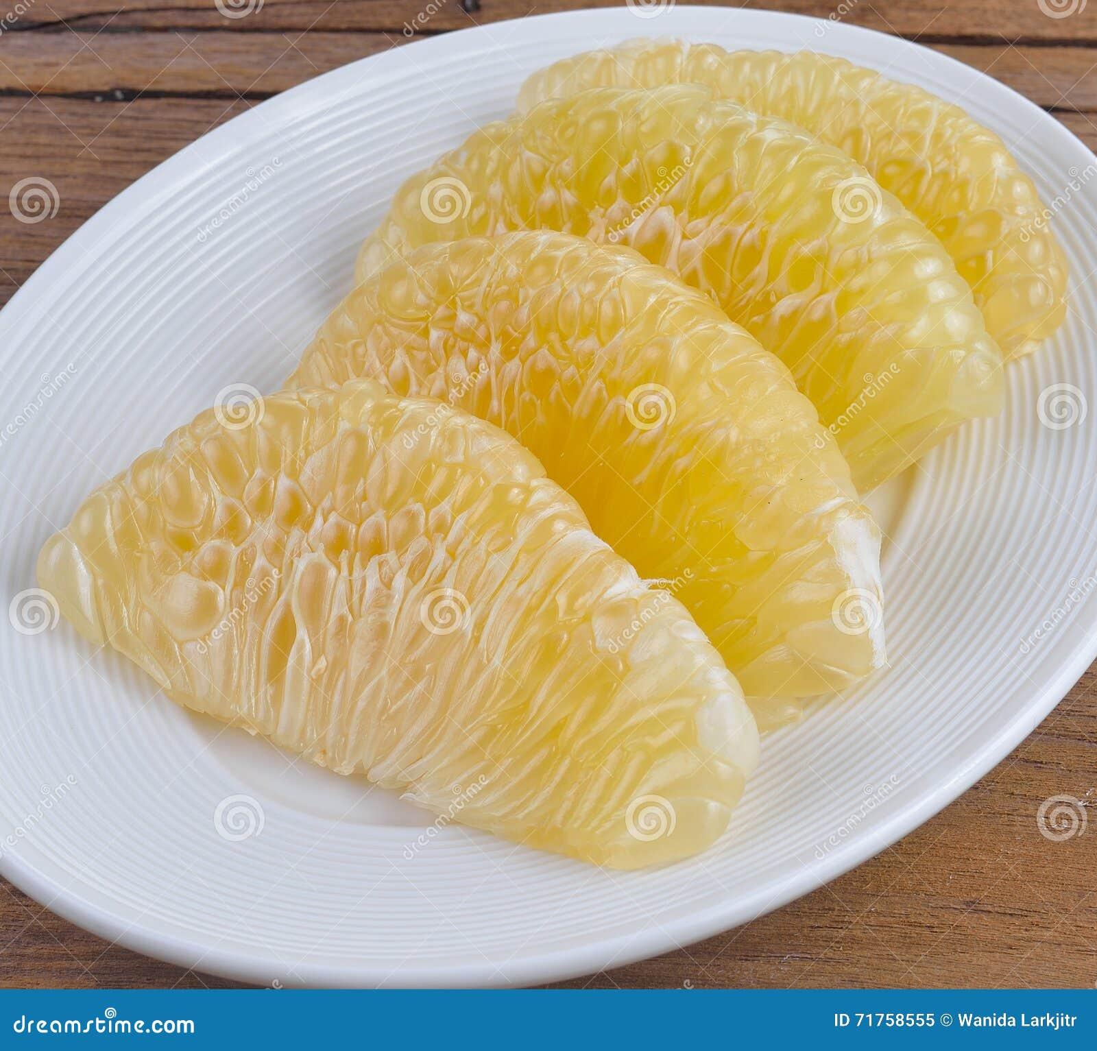 Φέτες του φρέσκου γκρέιπφρουτ σε ένα άσπρο πιάτο
