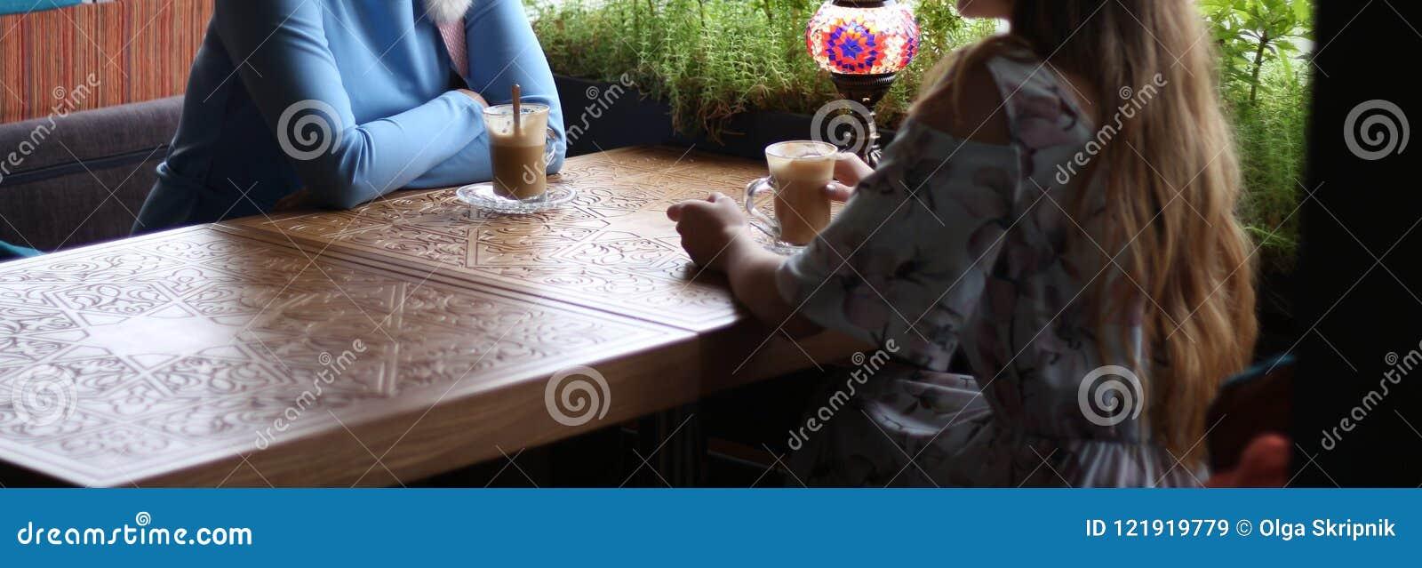 Φίλες που απολαμβάνουν στον καφέ από κοινού Νέες γυναίκες που συναντιούνται σε έναν καφέ συνεδρίαση δύο γυναίκες σε έναν καφέ για