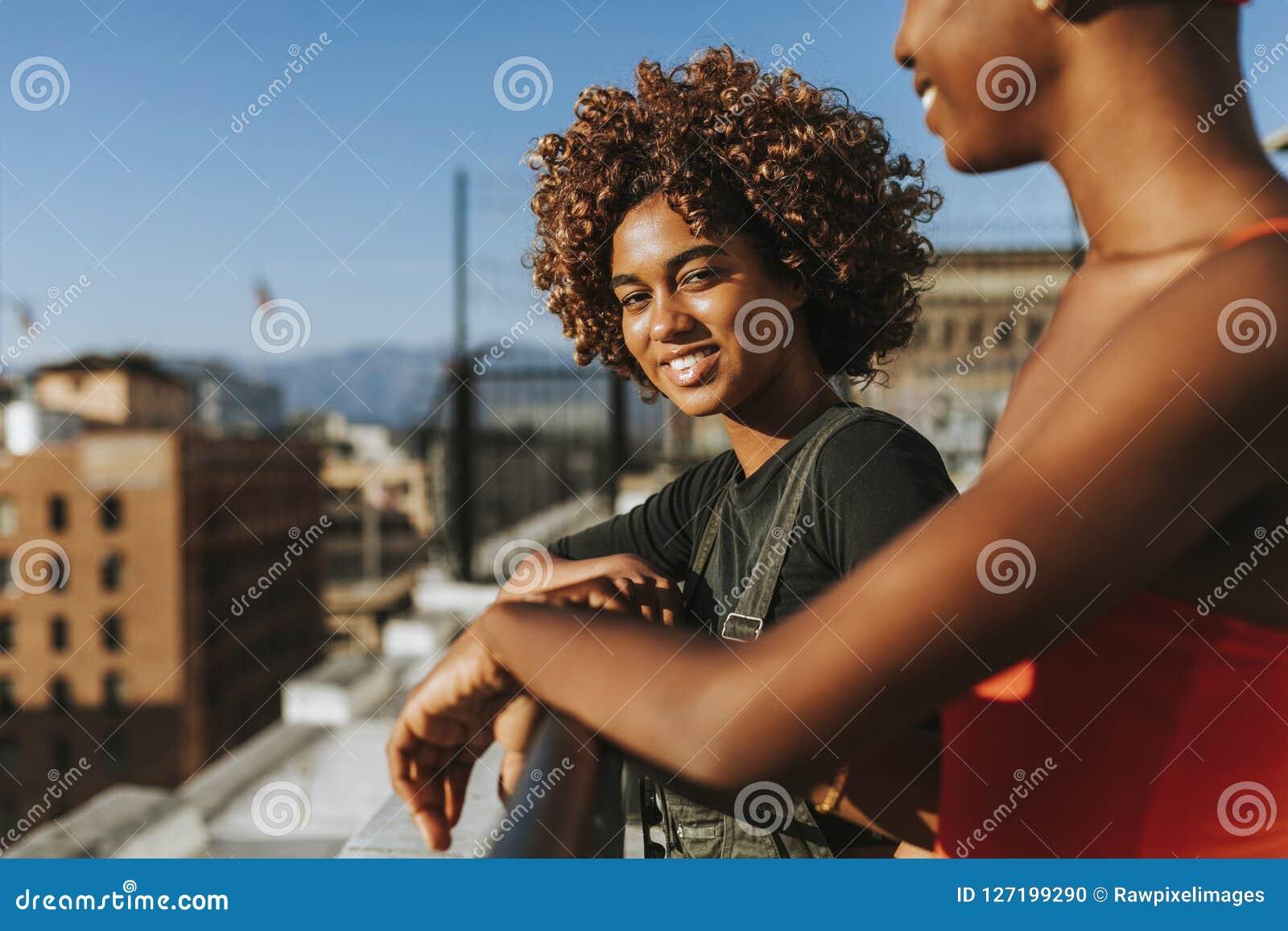 Φίλες που κρεμούν έξω σε μια στέγη Λα