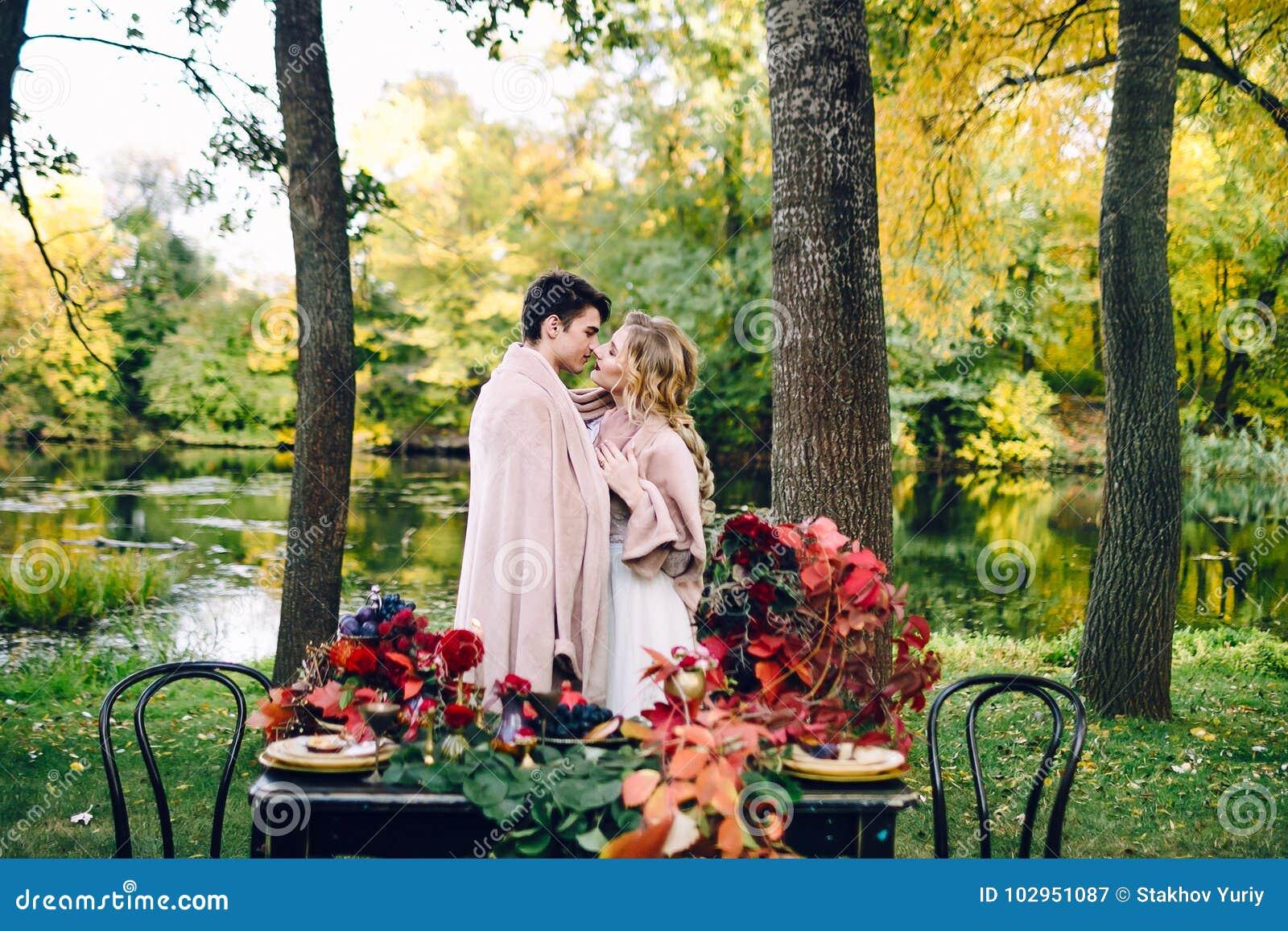 Φίλημα Newlyweds κάτω από το καρό δίπλα στον εορταστικό πίνακα Νύφη και νεόνυμφος στο πάρκο Γάμος φθινοπώρου _