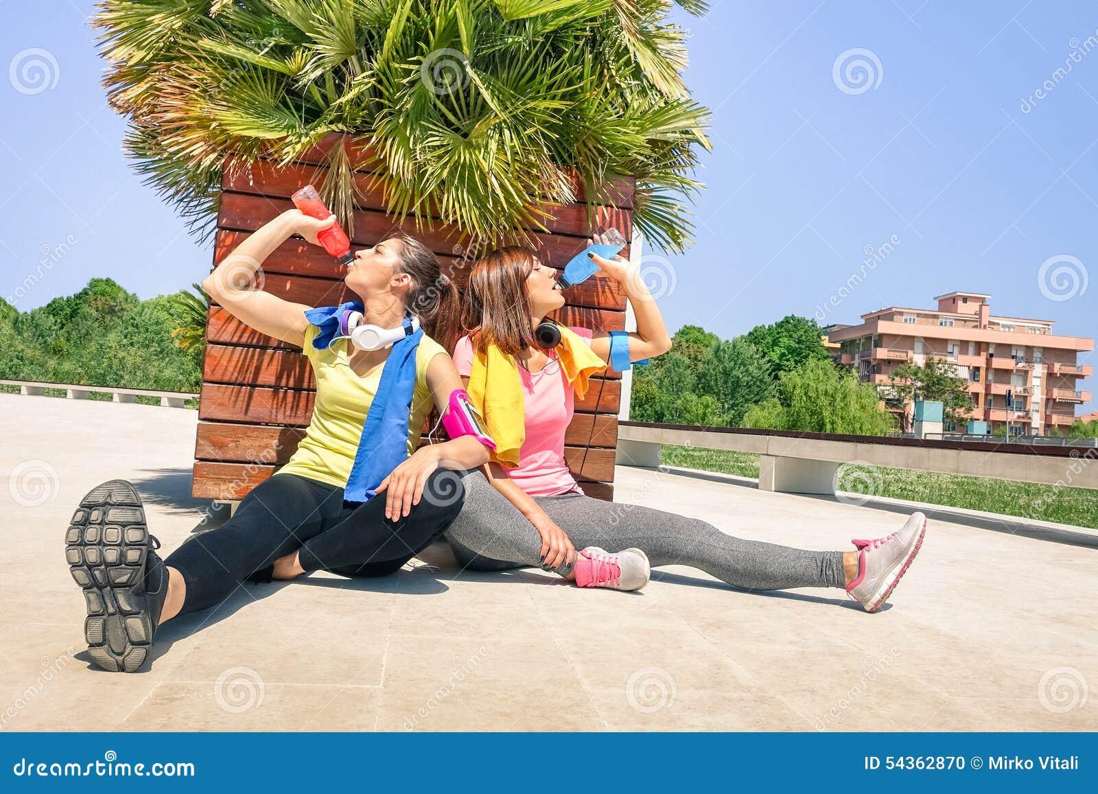 Φίλαθλες νέες γυναίκες που πίνουν τον ενεργητικό χυμό στην κατάρτιση τρεξίματος