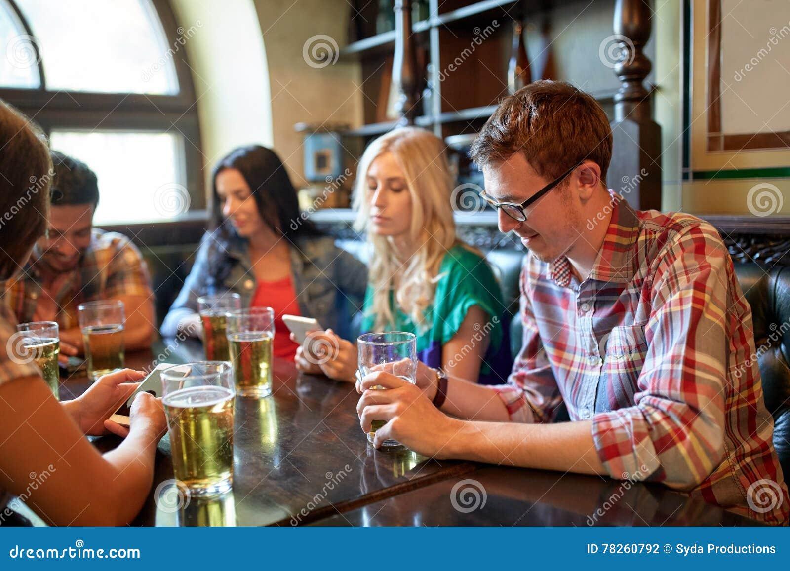 Φίλοι με τα smartphones και μπύρα στο φραγμό ή το μπαρ