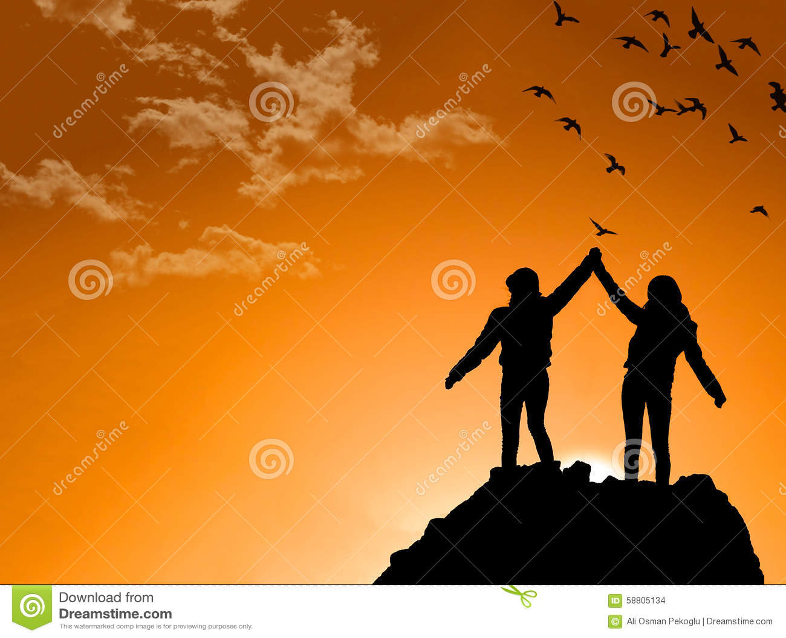 Φίλοι πάνω από ένα βουνό που τινάζει τα αυξημένα χέρια
