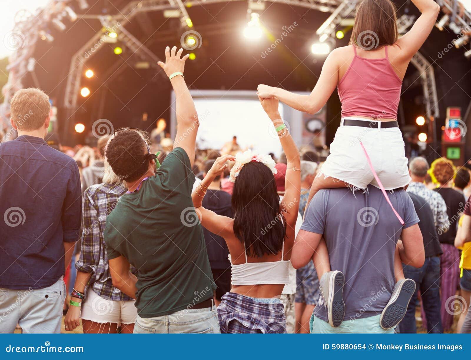 Φίλοι που έχουν τη διασκέδαση στο πλήθος στο φεστιβάλ μουσικής, πίσω άποψη